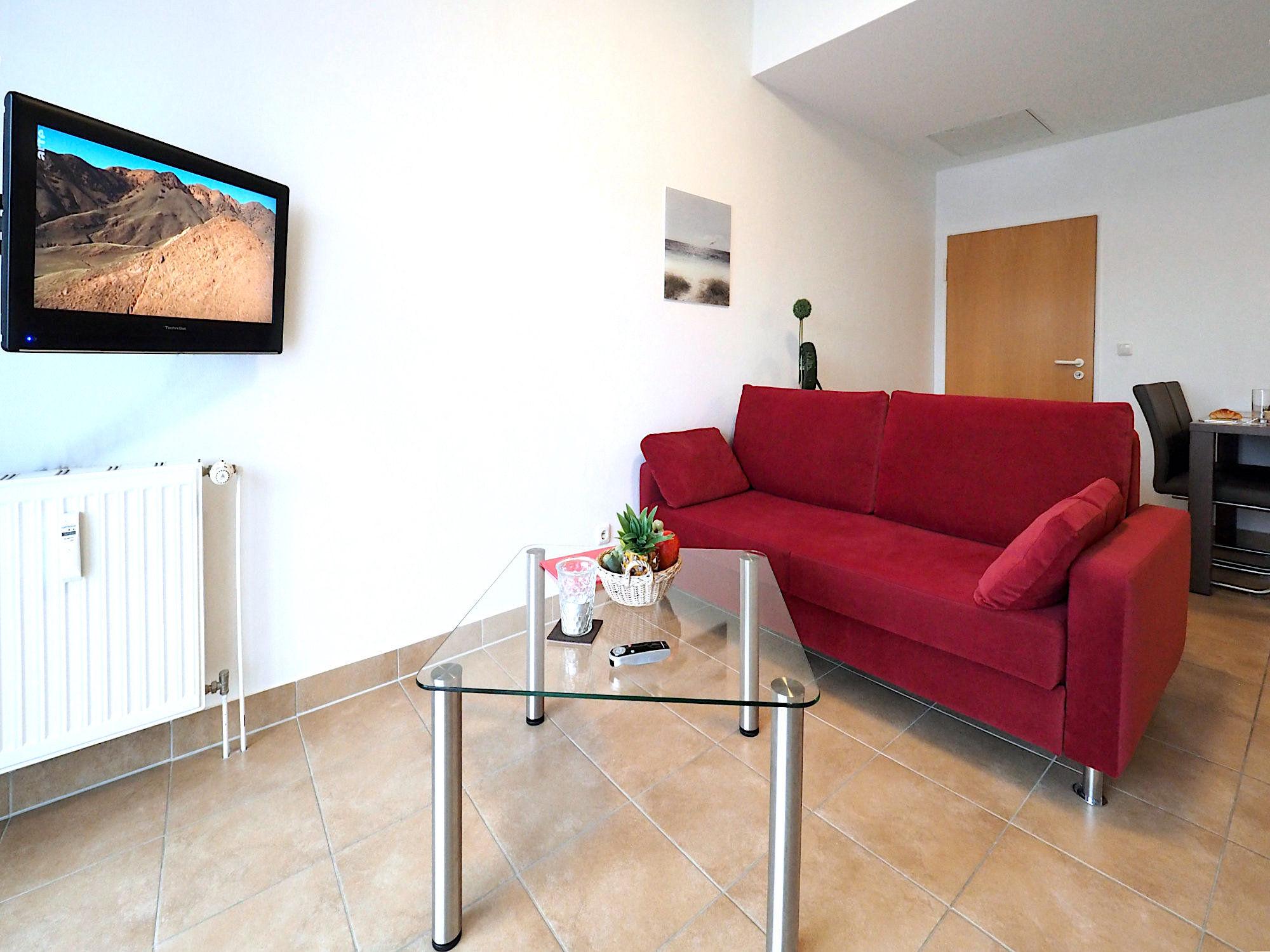 Wohnzimmer mit Couch, Glastisch und Flatscreen TV an der Wand hängend