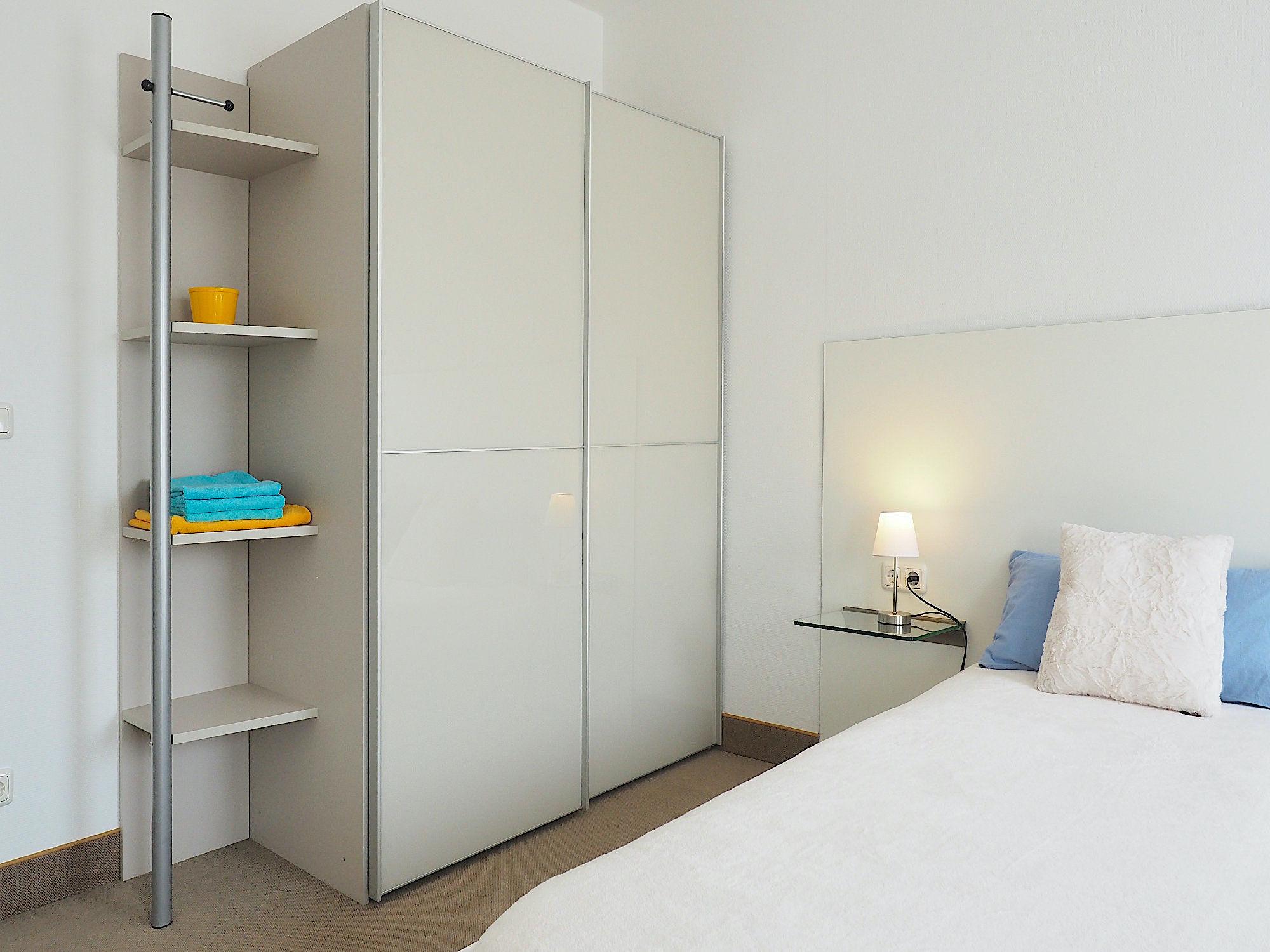 Schlafzimmer mit Doppelbett, dahinter ein großer Kleiderschrank mit Regalteil