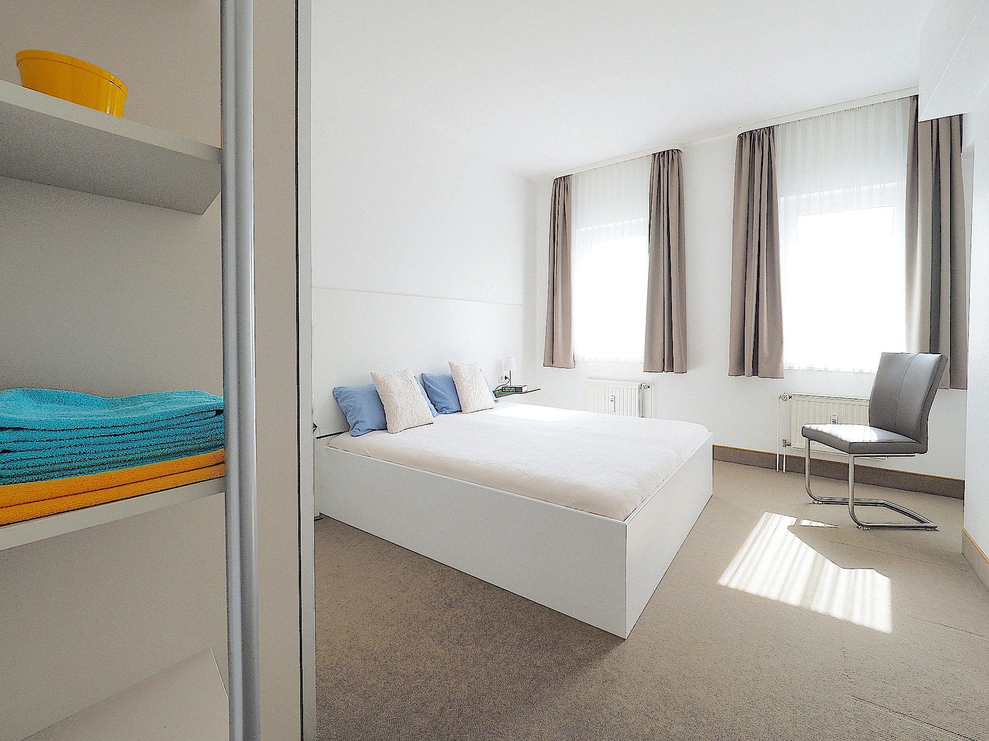 Schlafzimmer mit Doppelbett, links davon ein Regal, im Hintergrund zwei große  Fenster
