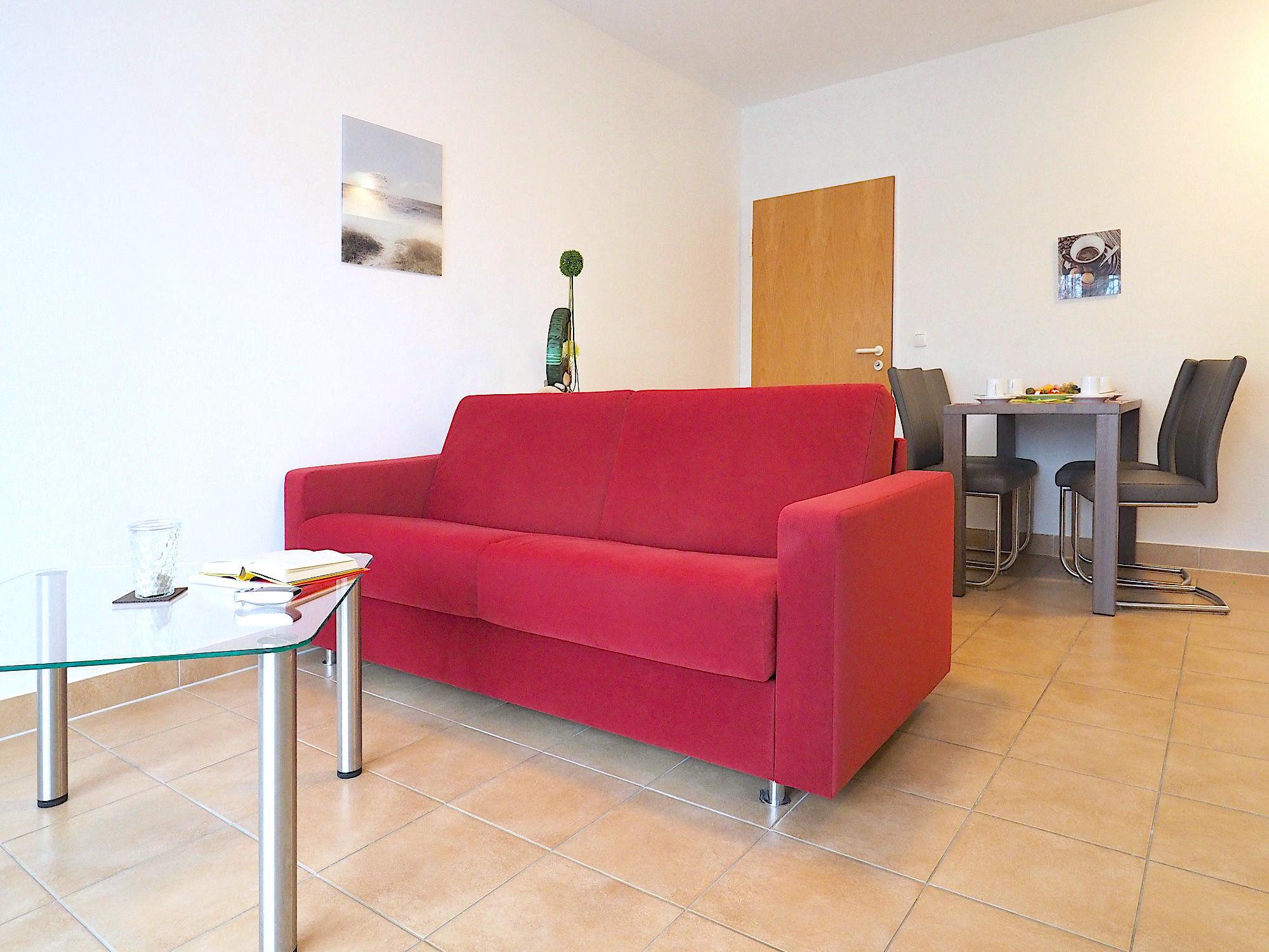 Wohnzimmer mit Couch, im Hintergrund ein Esstisch mit Stühlen