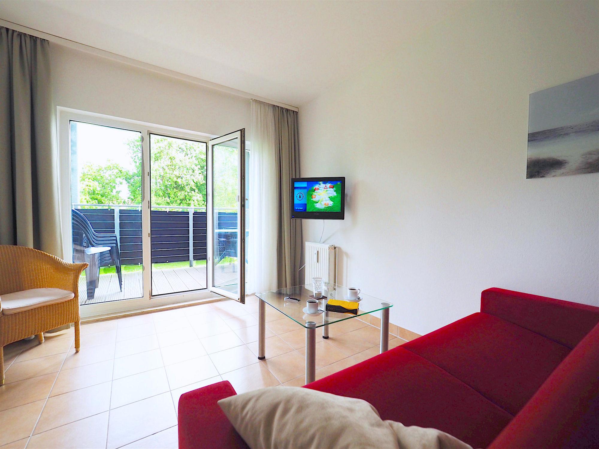 Wohnzimmer mit Couch, Glastisch und Flatscreen TV, an der Wand hängend. Im Hintergrund bodentiefe Fenster und Balkon