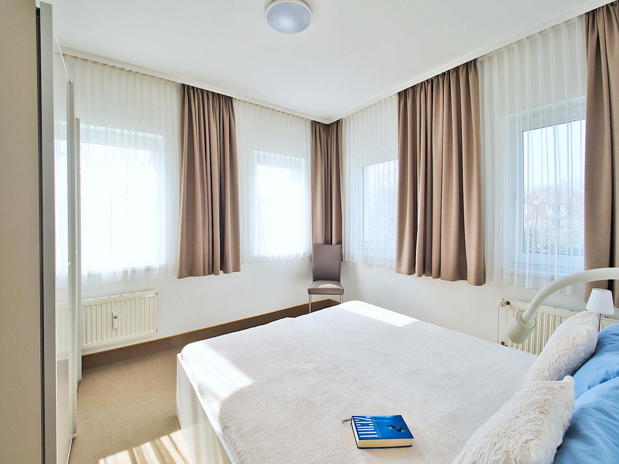 Zweites Schlafzimmer mit Doppelbett, an zwei Wänden jeweils 2 Fenster, links ein großer Kleiderschrank