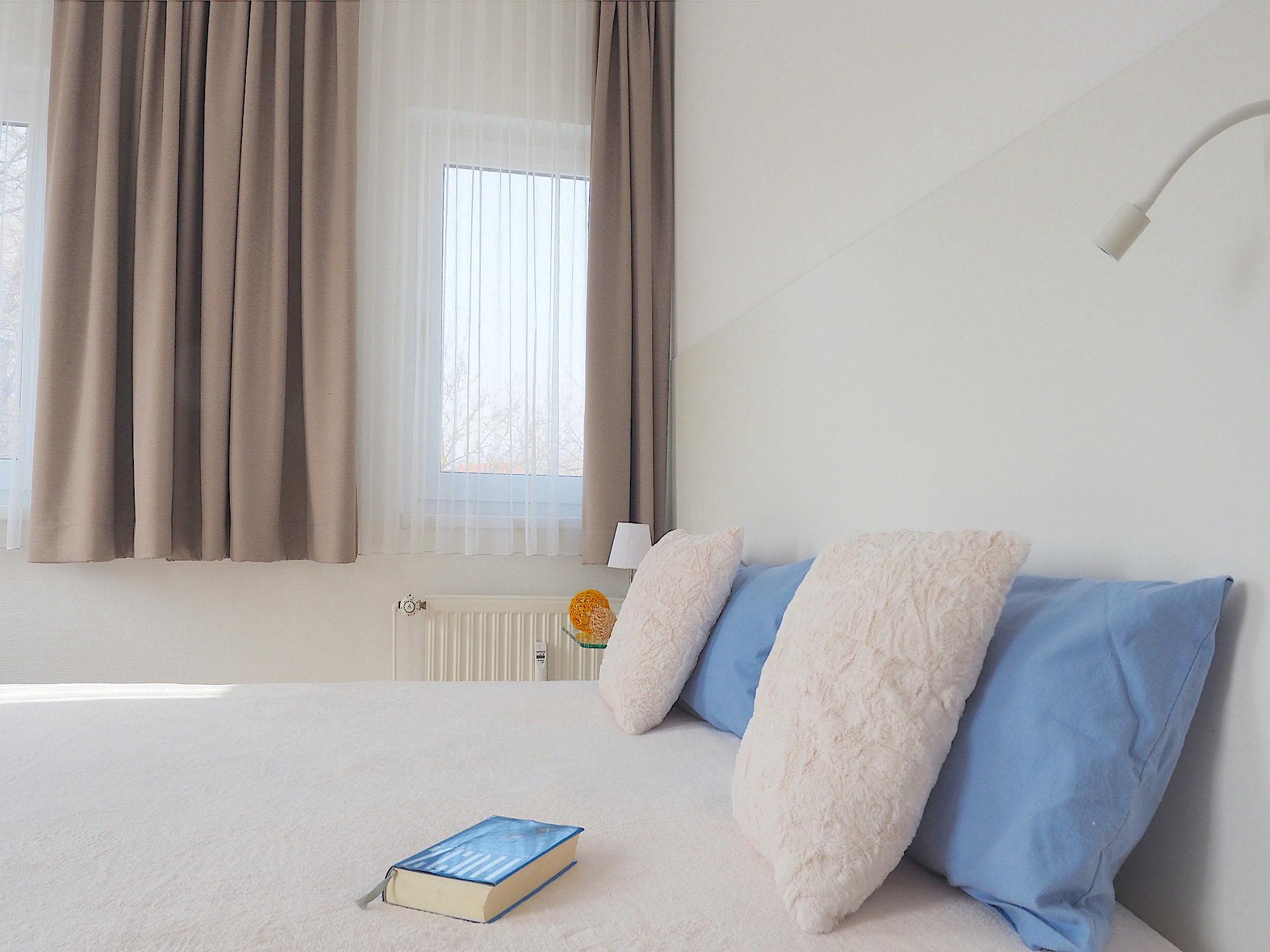 Zweites Schlafzimmer mit Doppelbett, hinter dem Kopfende ein breites Fenster