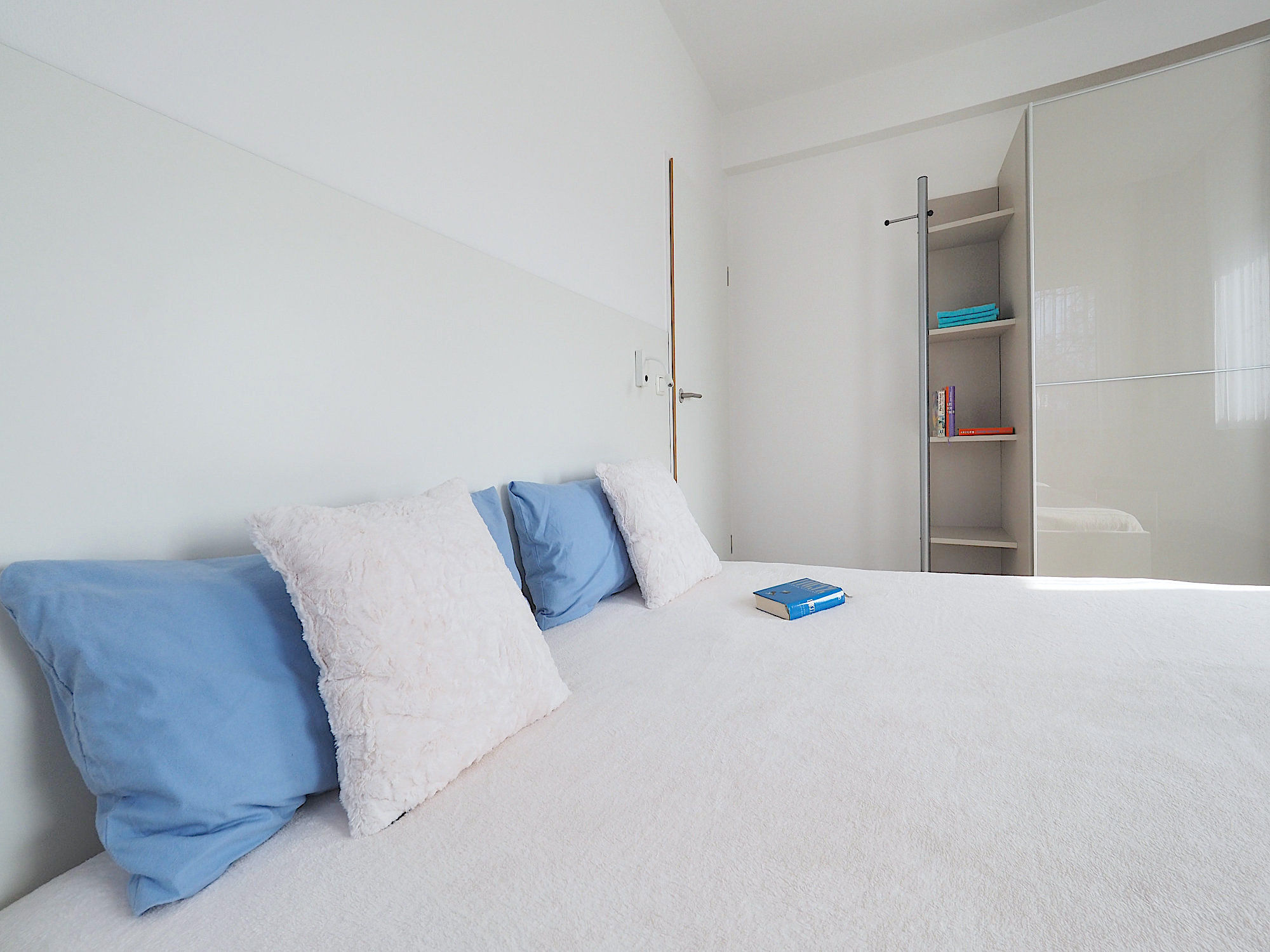 Zweites Schlafzimmer mit Doppelbett, dahinter ein großer Kleiderschrank mit Schiebetüren und Regalteil