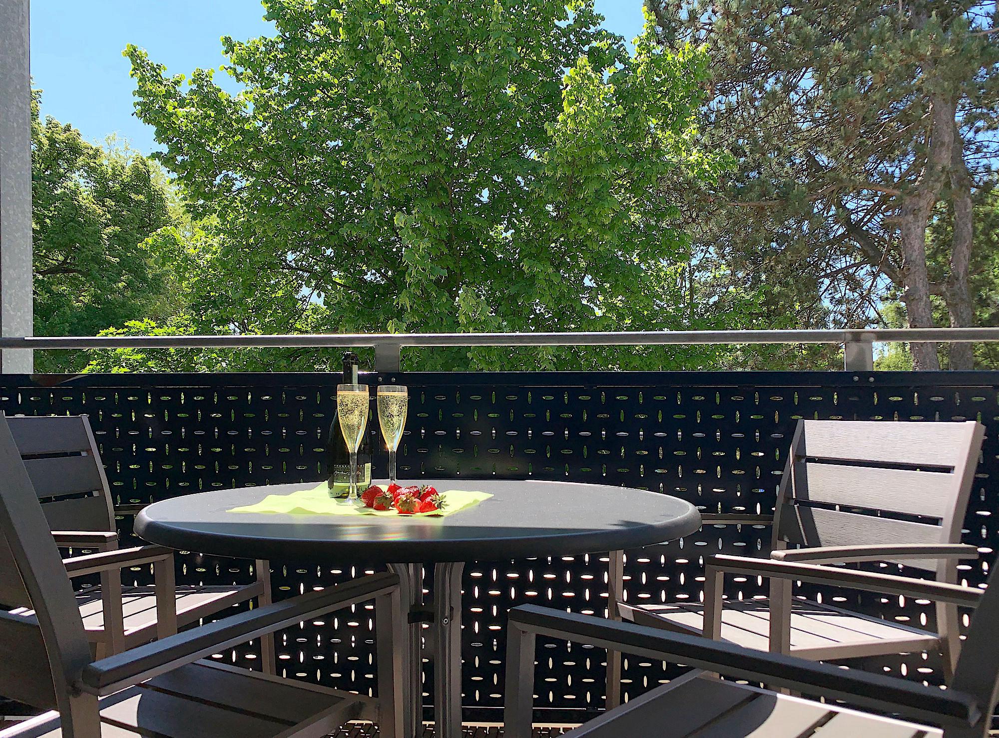Balkon mit Tisch und Stühlen und Blick in`s Grüne