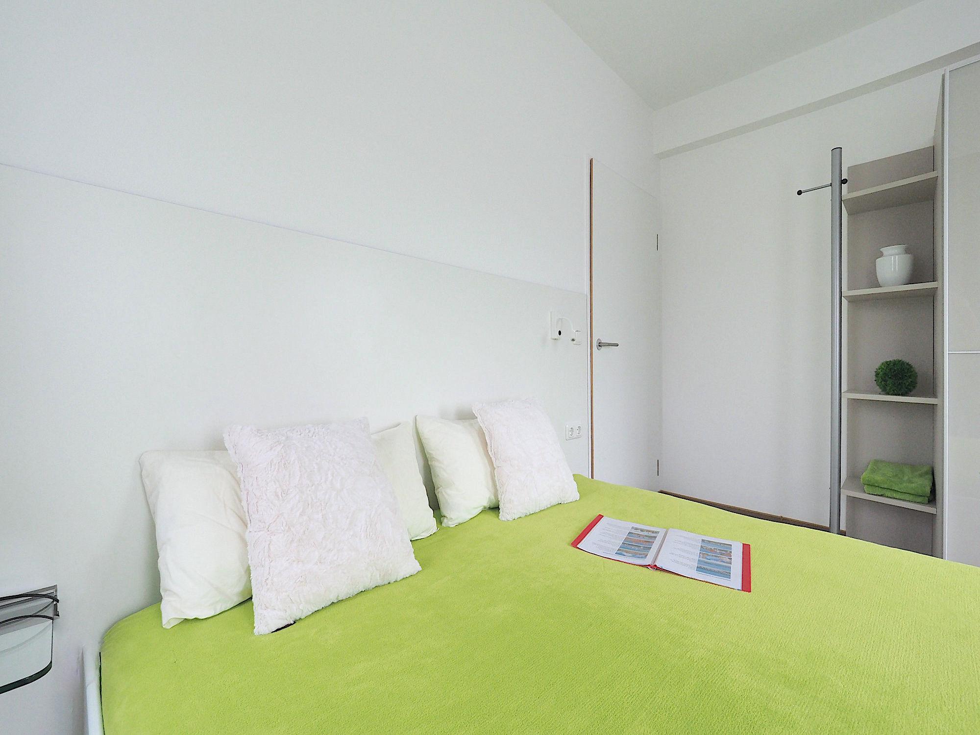 Zweites Schlafzimmer mit Doppelbett, dahinter ein großer Kleiderschrank mit Regalteil