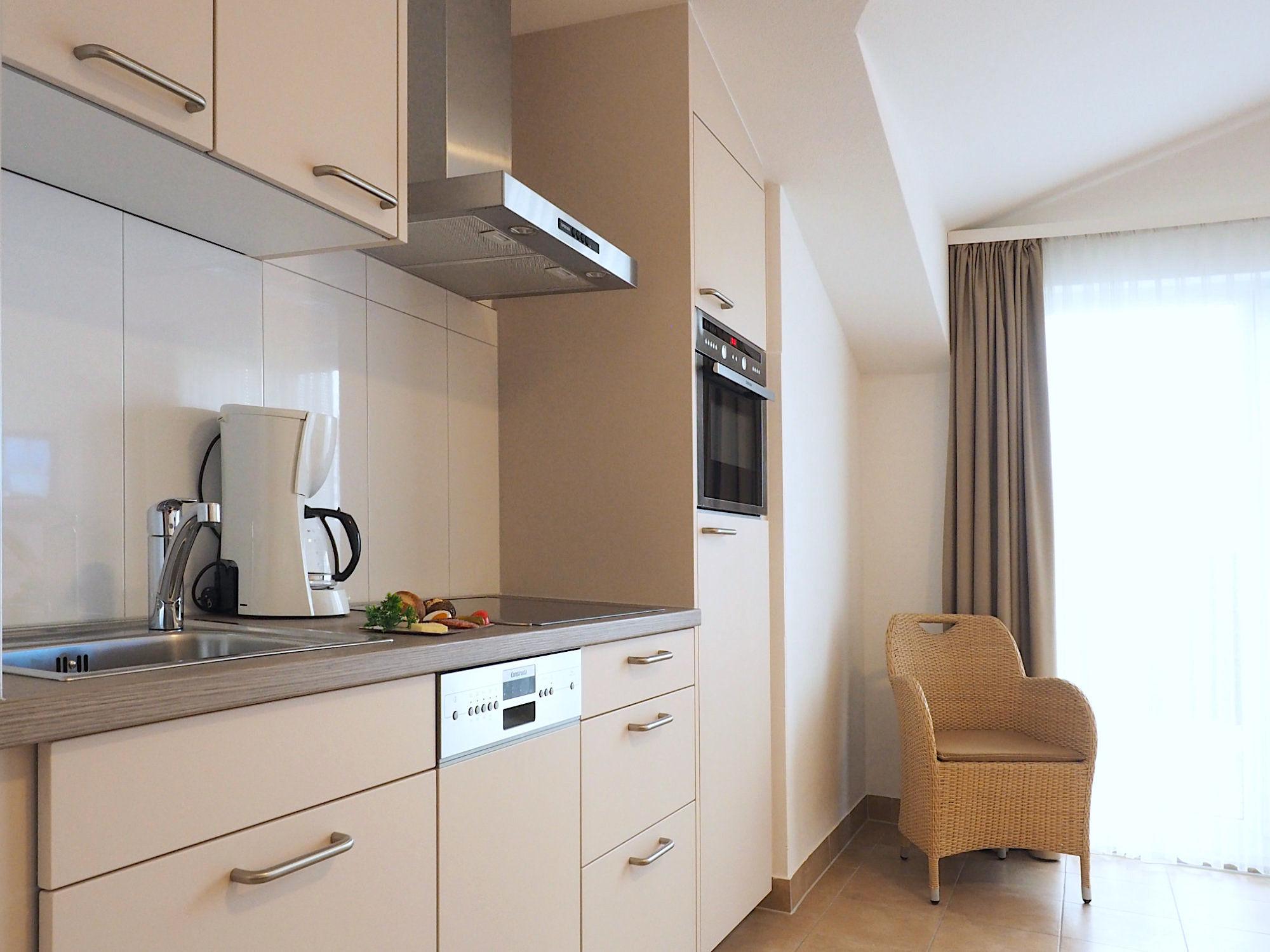 Moderne Küchenzeile mit elektrischen Geräten, rechts daneben bodentiefes Fenster