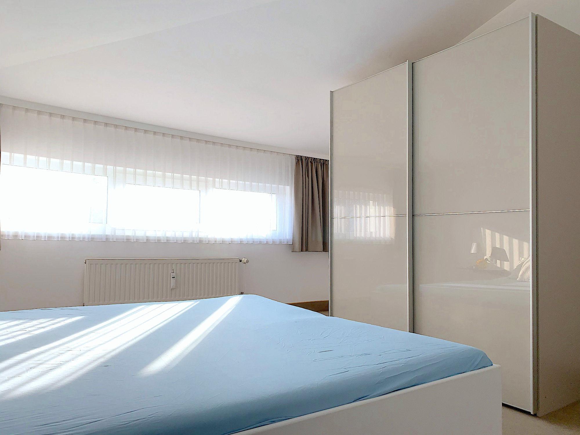 Schlafzimmer mit Doppelbett, rechts davon ein großer Kleiderschrank mit Schiebetüren, im Hintergrund ein breites Fenster