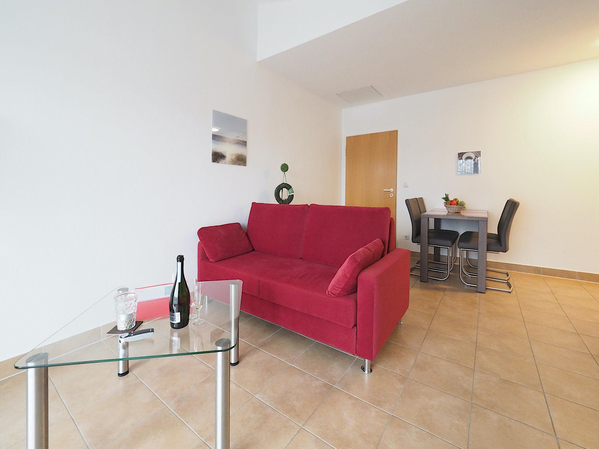 Wohnzimmer mit Couch und Glastisch, im Hintergrund ein Esstisch mit Stühlen