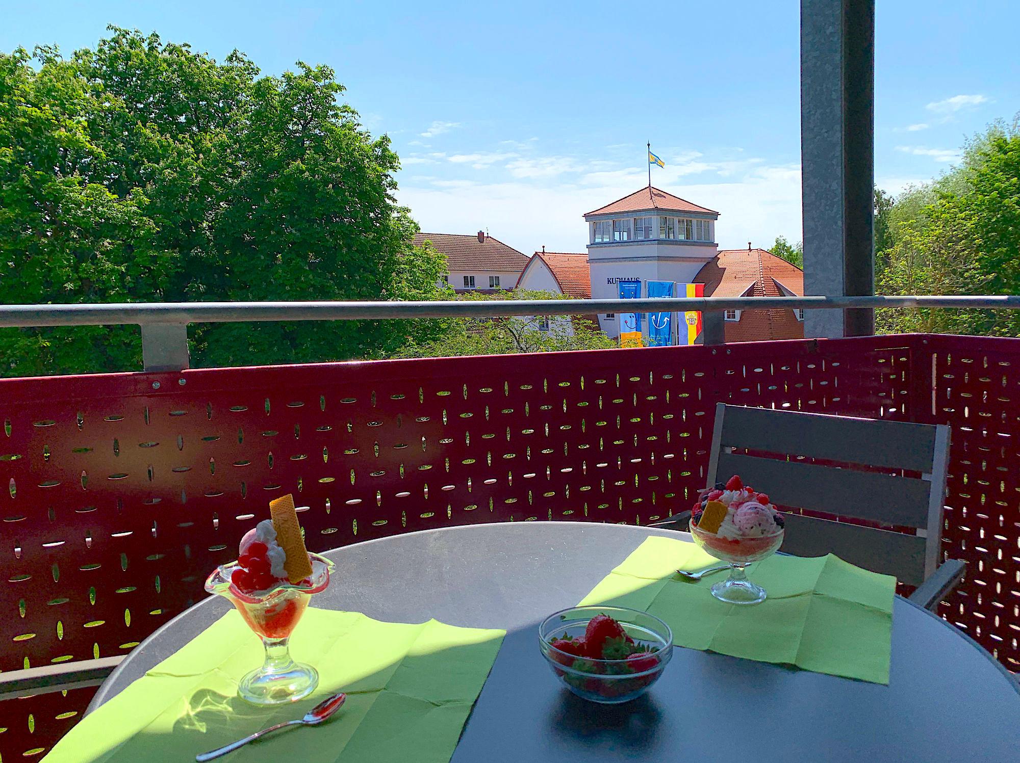 Balkon mit Tisch und Stühlen und Blick zum Kurhaus