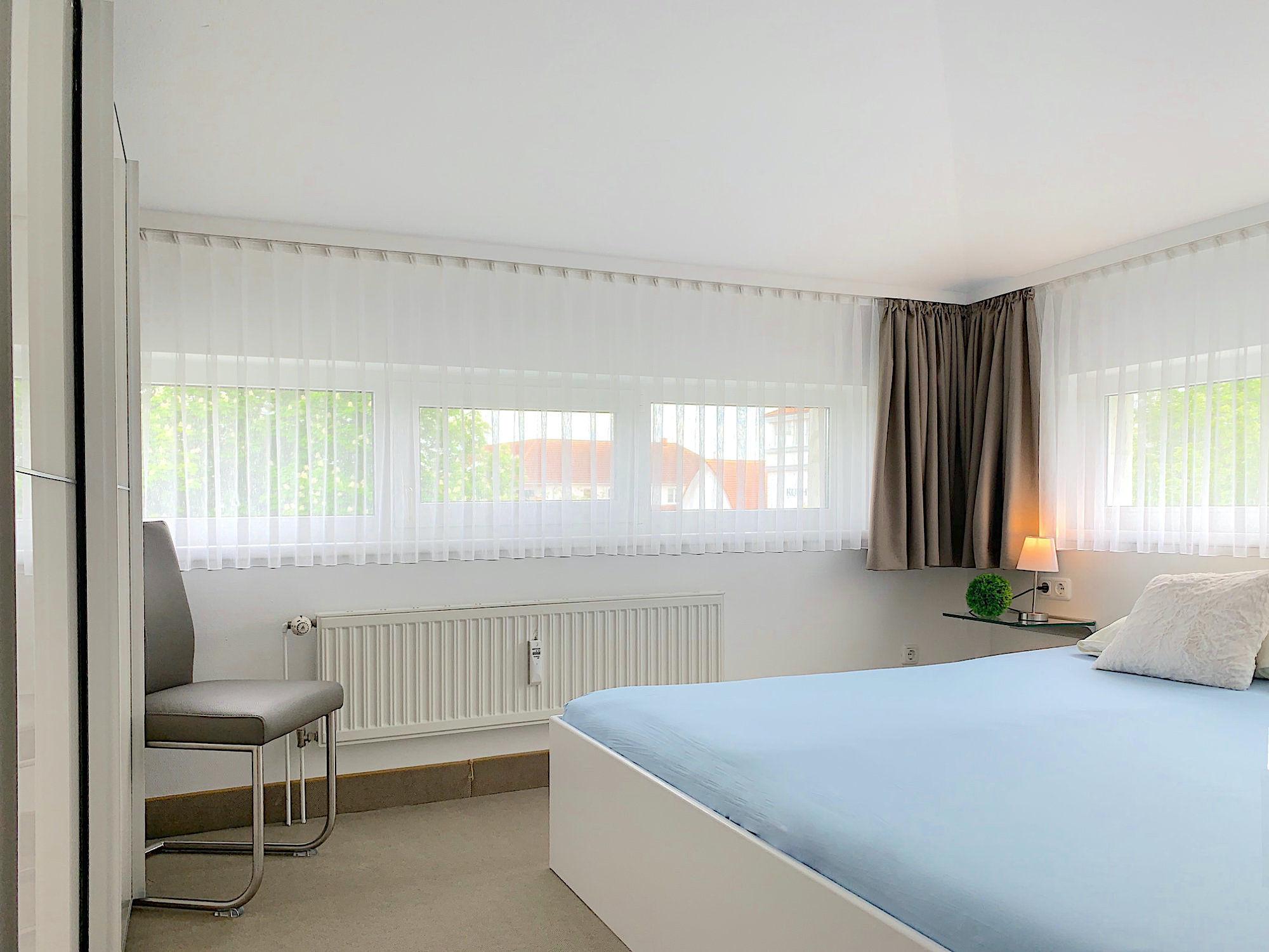 Schlafzimmer mit Doppelbett, an zwei Wänden jeweils 2 Fenster, links befindet sich ein großer Kleiderschrank