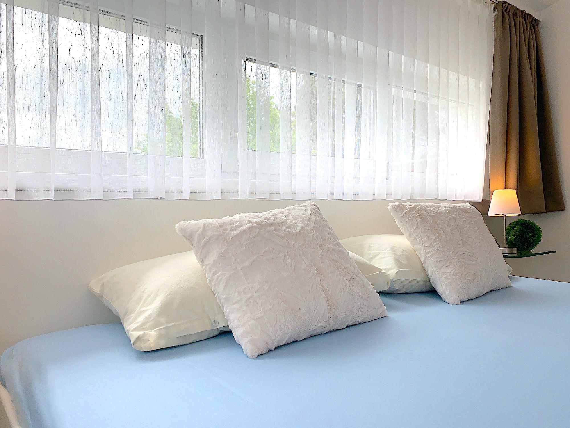 Schlafzimmer mit Doppelbett, hinter dem Kopfende ein breites Fenster