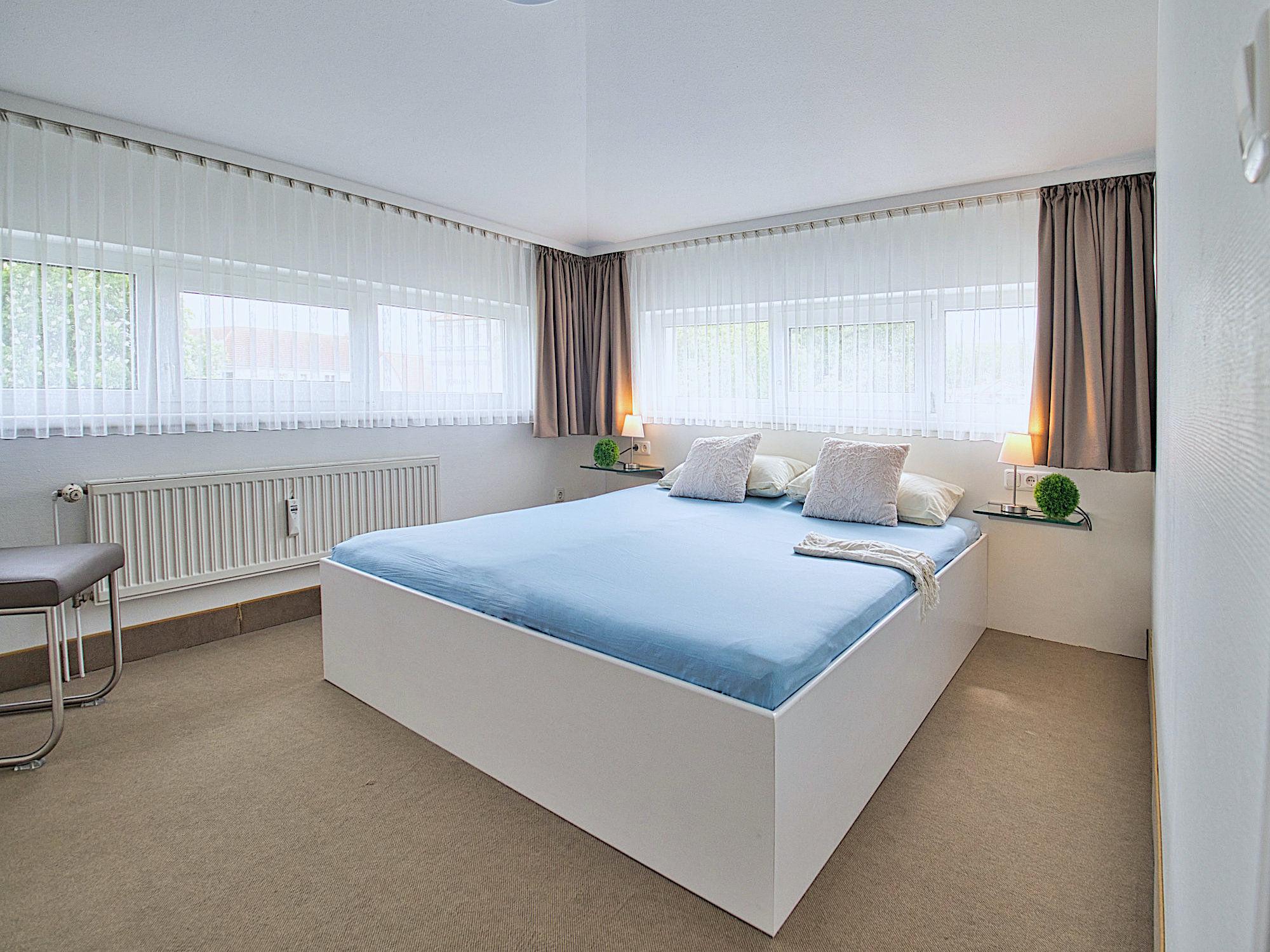 Schlafzimmer mit Doppelbett, an zwei Wänden jeweils 2 Fenster