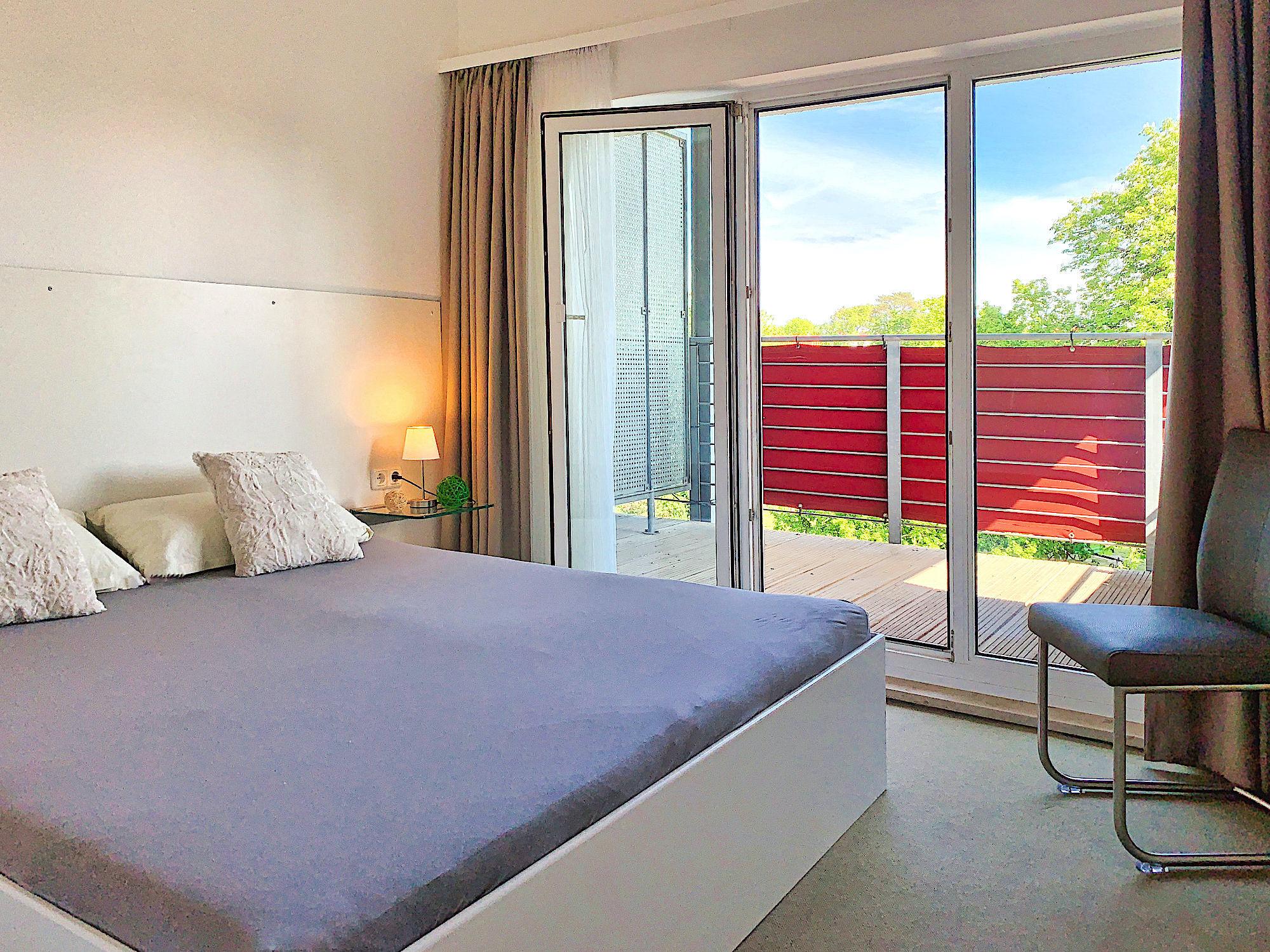 Zweites Schlafzimmer mit Doppelbett, rechts davon bodentiefe Fenster und Zugang zum Balkon