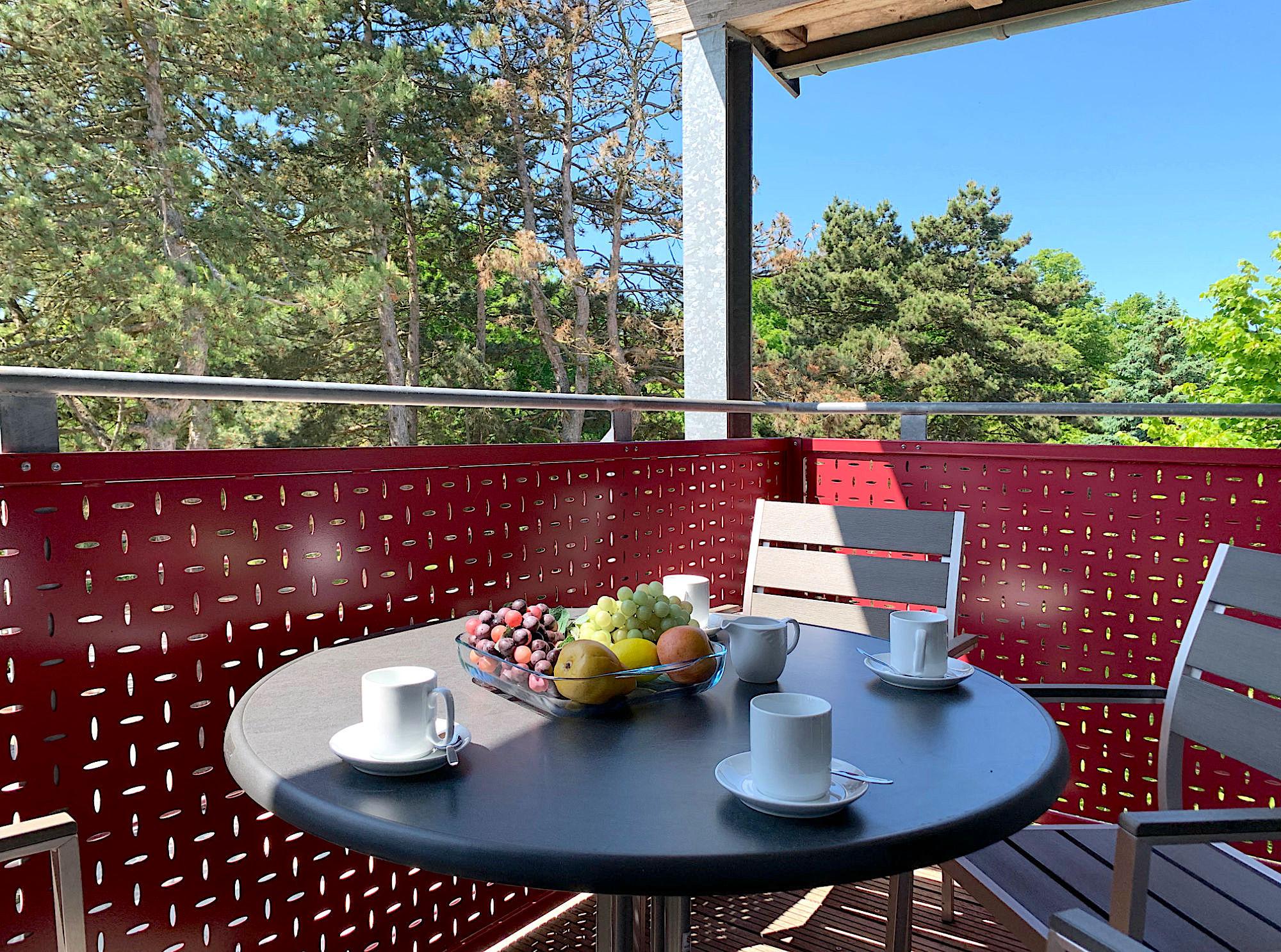 Balkon mit Tisch und Stühlen und Blick ins Grüne