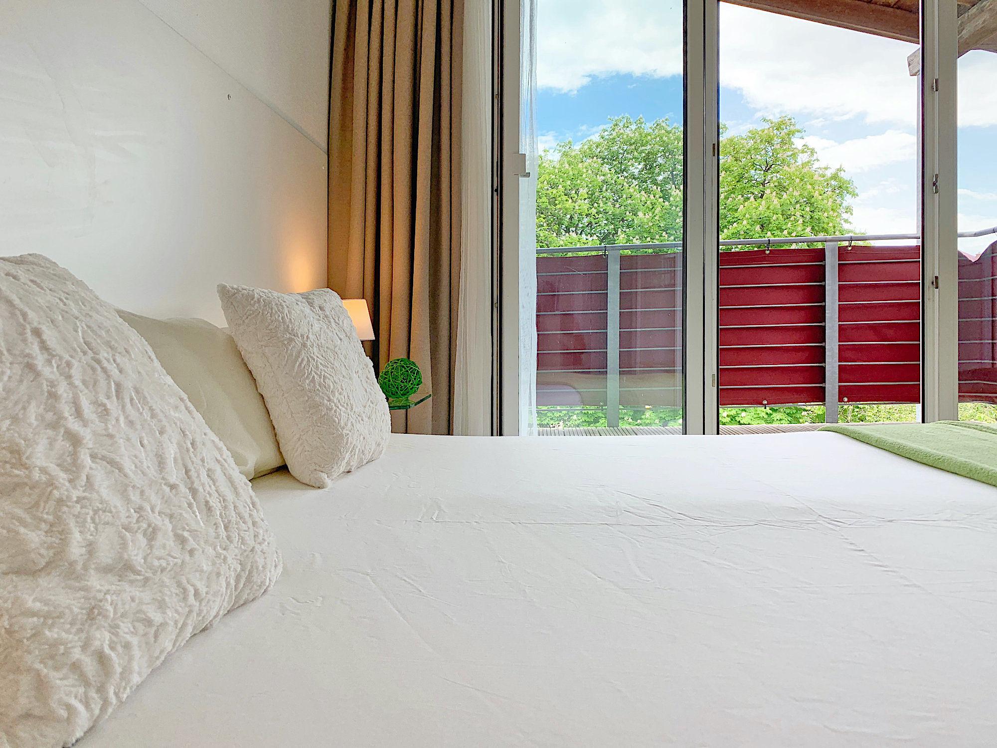 Schlafzimmer mit Doppelbett, Kopfteil mit Kopfkissen, dahinter bodentiefe Fenster mit Zugang zum Balkon