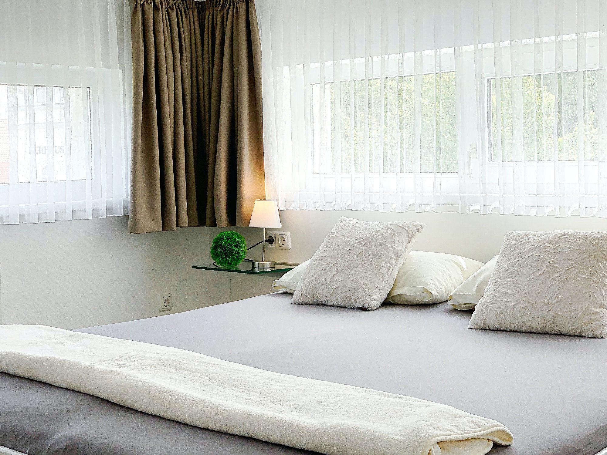 Zweites Schlafzimmer mit Doppelbett, an zwei Wänden mehrere Fenster