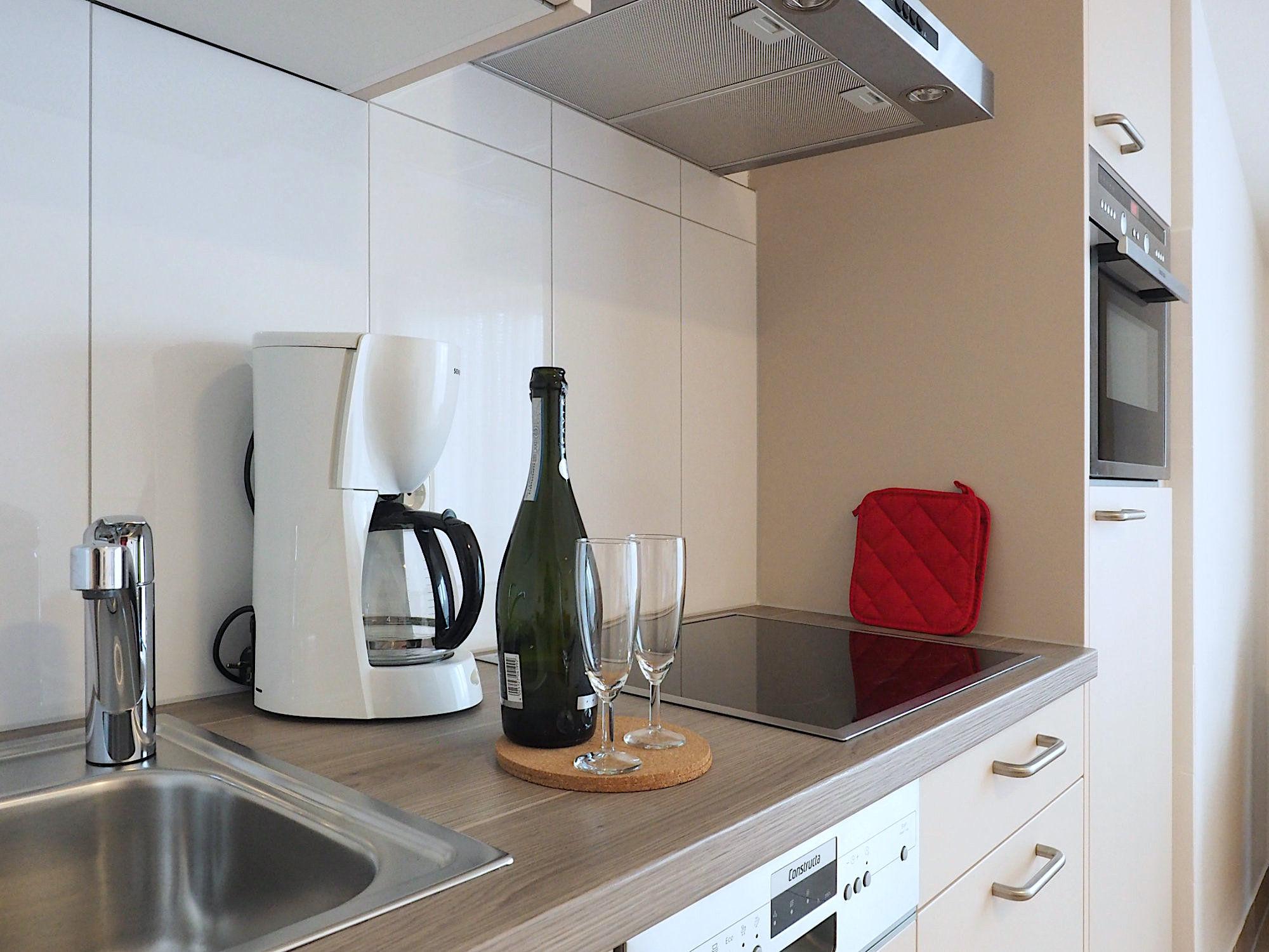 Moderne Küchenzeile mit elektrischen Geräten und Deko