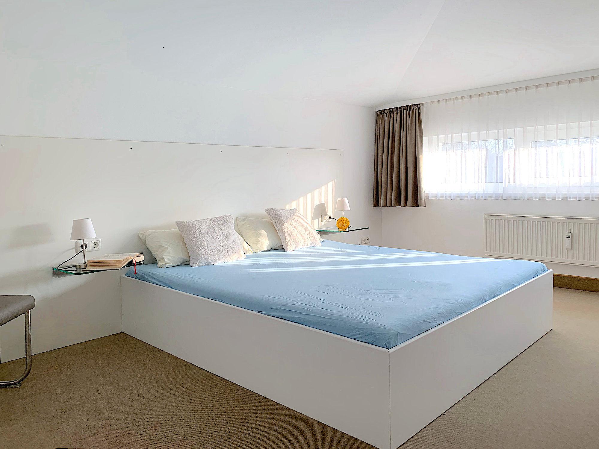Schlafzimmer mit Doppelbett, im Hintergrund ein breites Fenster