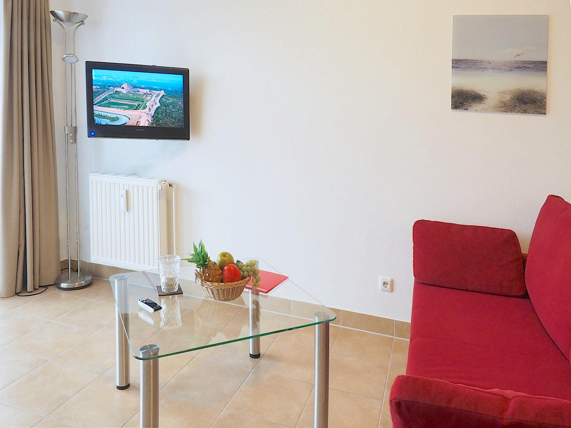 Wohnzimmer mit Couch, Glastisch und Flatscreen TV, an der Wand hängend