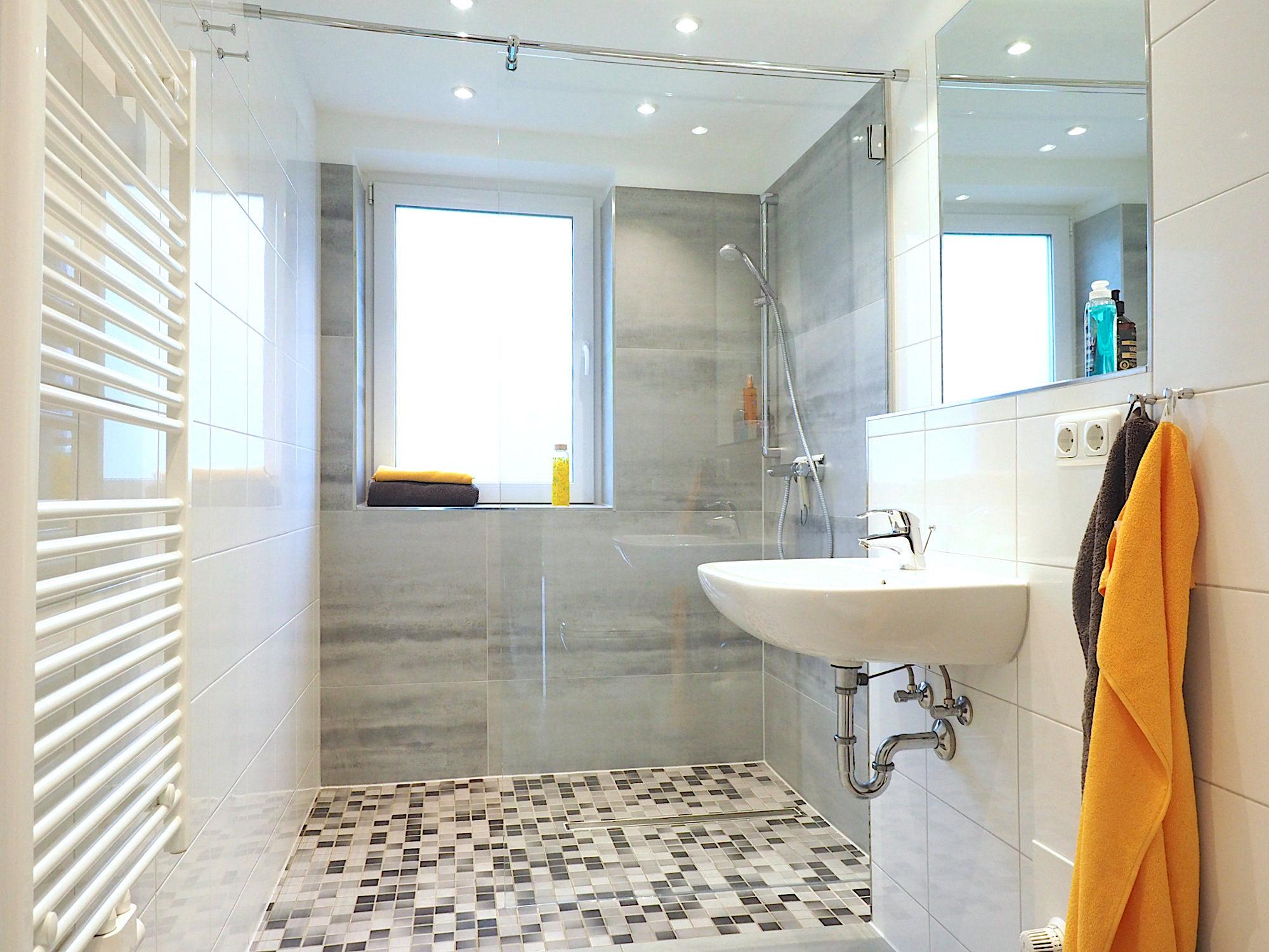Duschbad: rechts ein Waschbecken mit Spiegel, links eine Handtuchheizung, im Hintergrund eine bodentiefe Dusche mit Glaswand