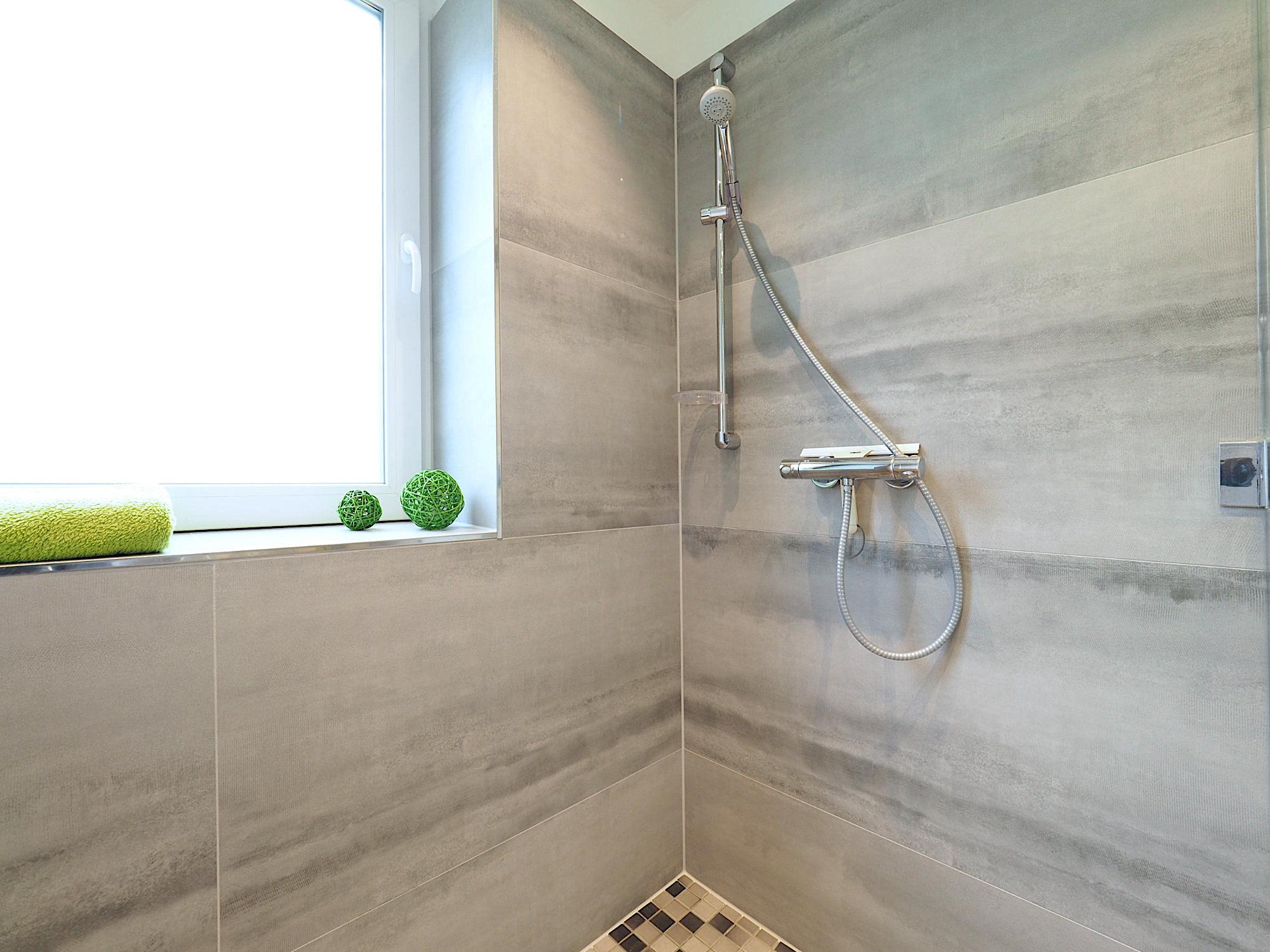 Blick in die geflieste Dusche mit Duscharmatur