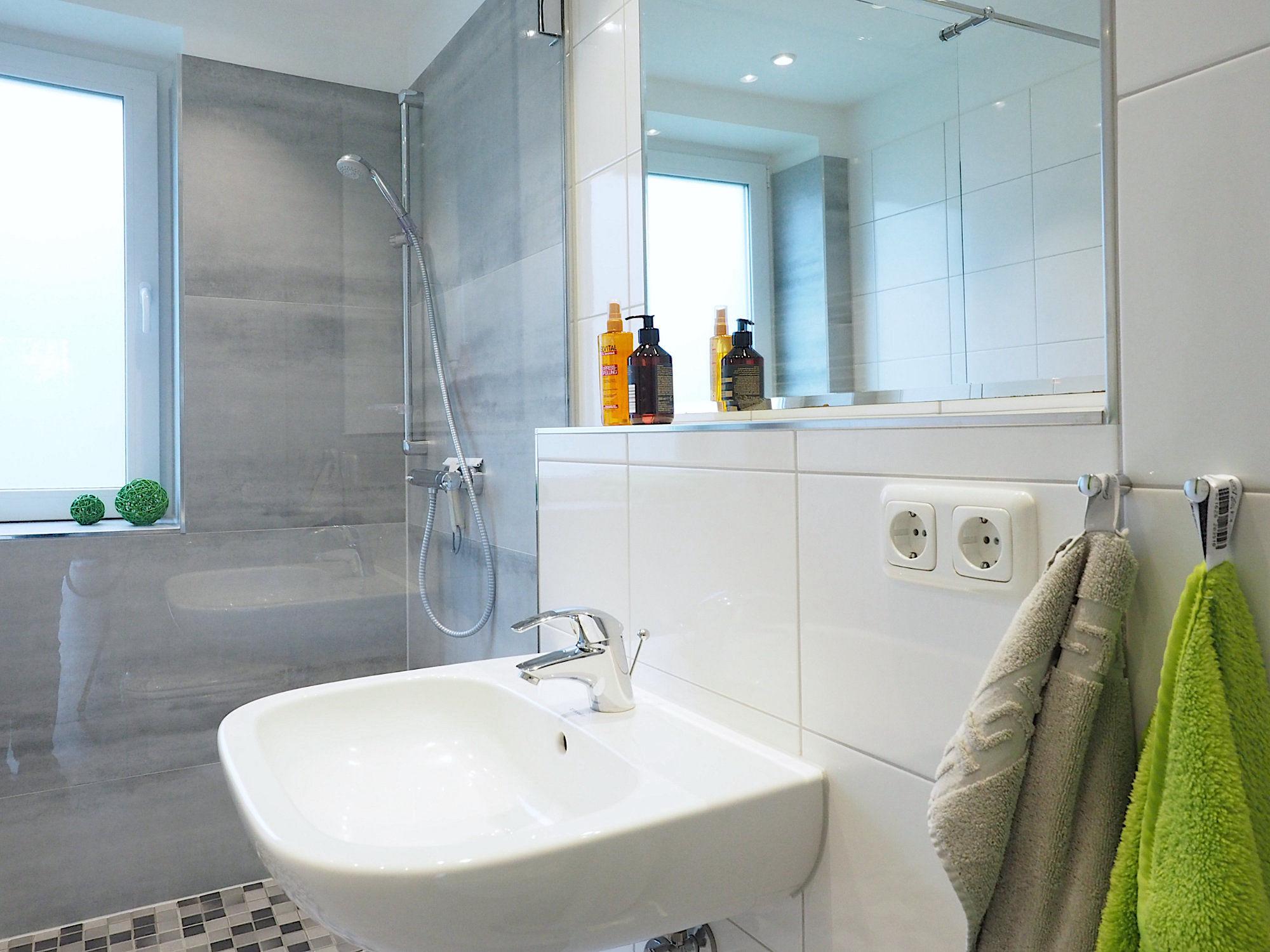 Duschbad: rechts ein Waschbecken mit Spiegel, im Hintergrund eine bodentiefe Dusche mit Glaswand