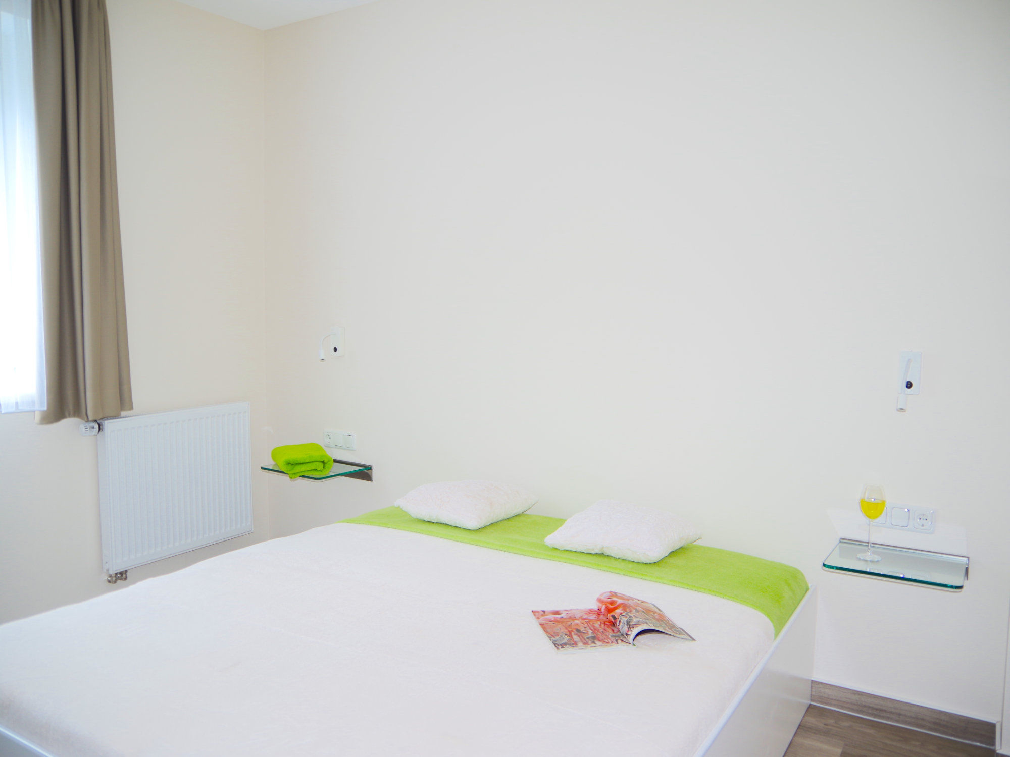Schlafzimmer mit Doppelbett und Glaskonsolen links und rechts vom Bett