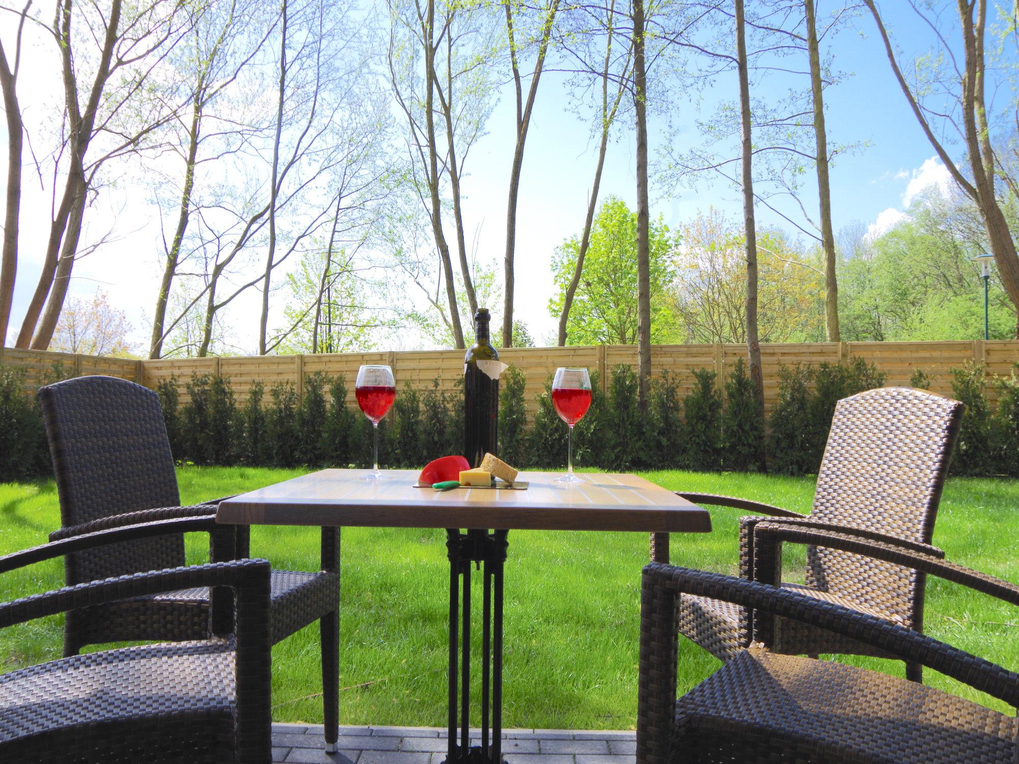Blick in den Garten mit Rasen, Bäumen im Hintergrund und Terrassenmöbeln, bestehend aus einem Tisch und Stühlen