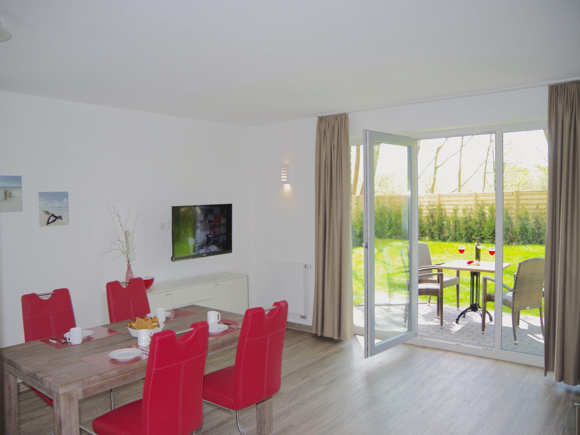 Links im Bild ein Esstisch mit 4 Stühlen, rechts davon ein Sideboard mit Flatscreen TV, weiter rechts bodentiefe Fenster