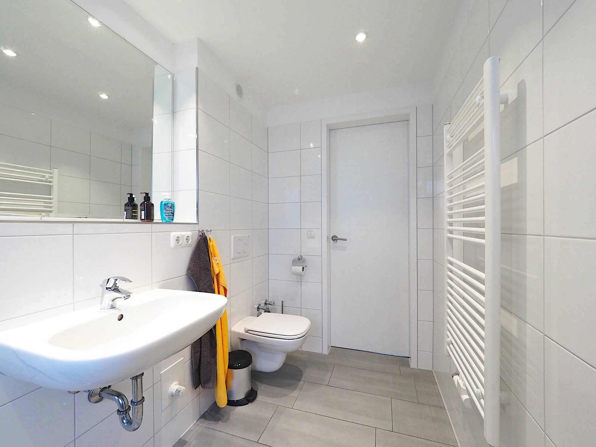 Duschbad von der Dusche aus gesehen, links ist ein Waschbecken mit Spiegel, rechts die Handtuchheizung