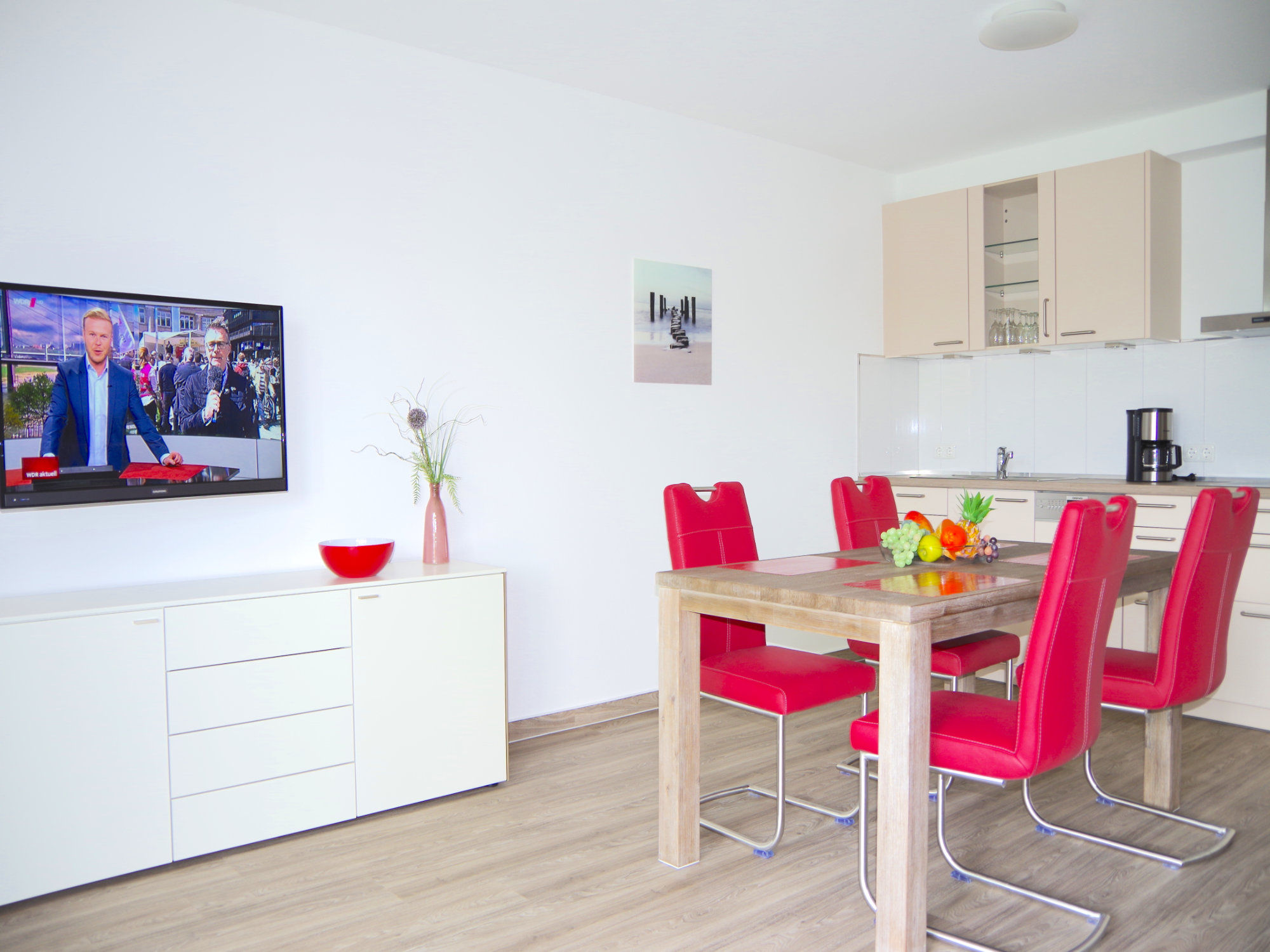 Links ist ein Sideboard mit Flatscreen TV, rechts der Esstisch mit 4 Stühlen. Dahinter ist eine moderne Küchenzeile