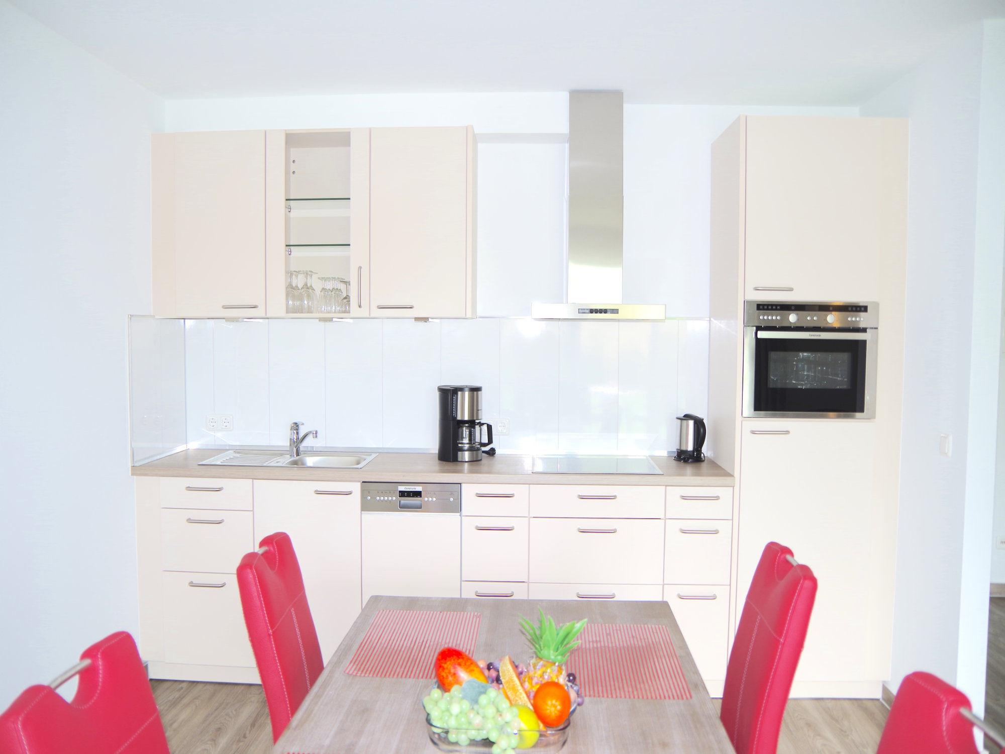 Esstisch mit vier Stühlen, dahinter ist eine moderne Küchenzeile mit elektrischen Geräten.