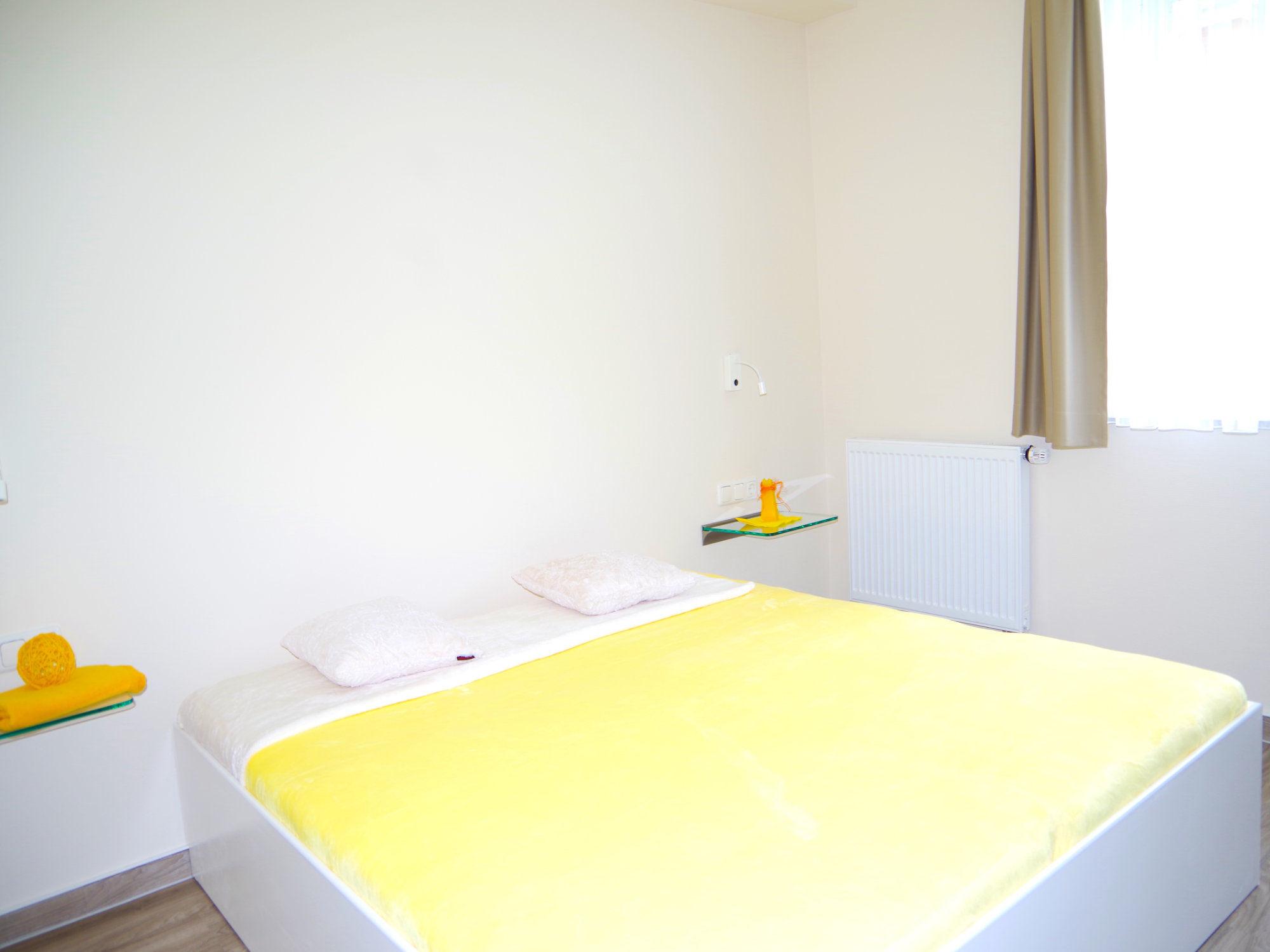Schlafzimmer mit Doppelbett und Glaskonsolen, rechts ist ein großes Fenster