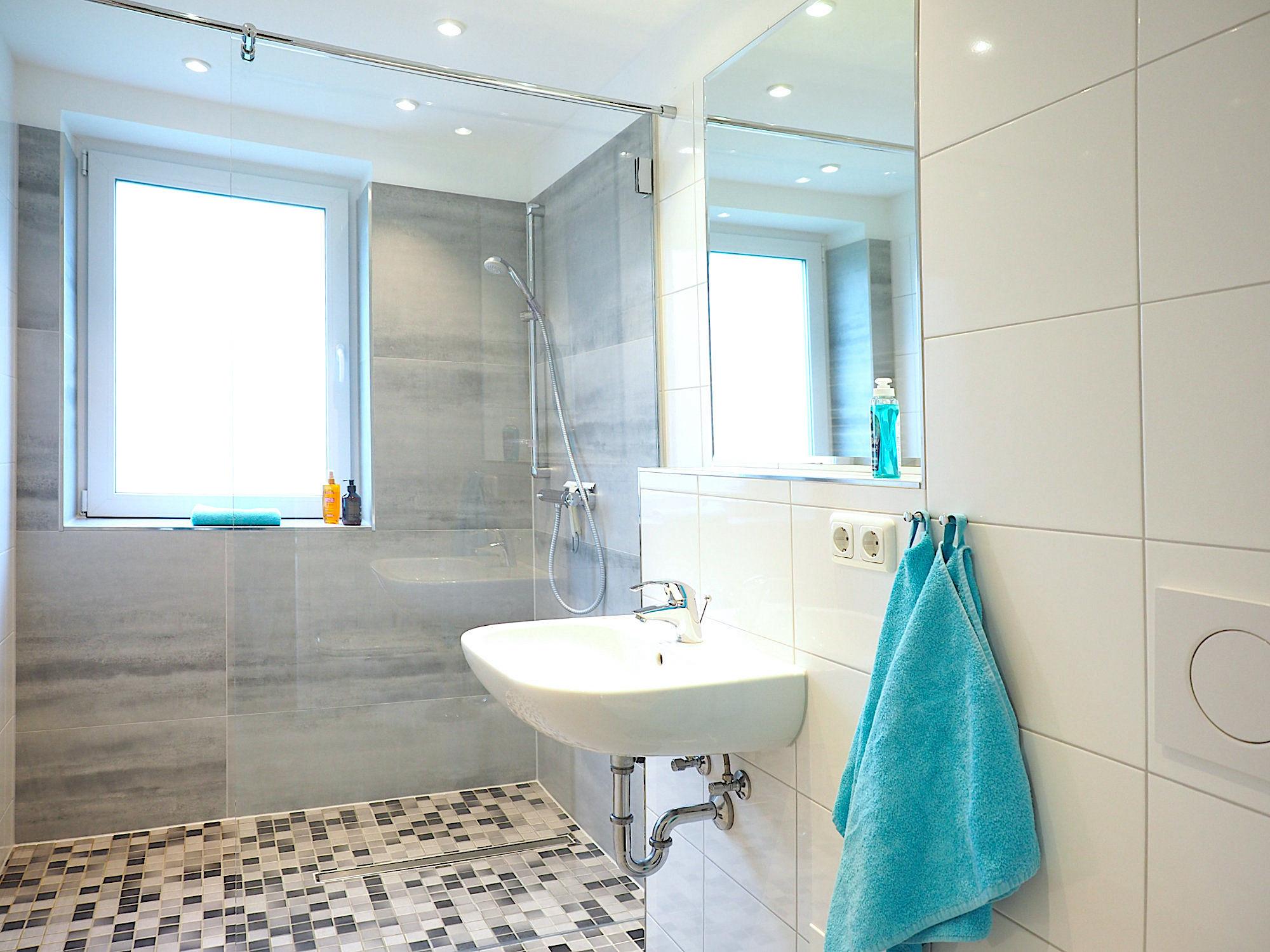 Duschbad: rechts ein Waschbecken mit Spiegel, im Hintergrund eine bodentiefe Dusche mit Glaswand sowie ein Fenster
