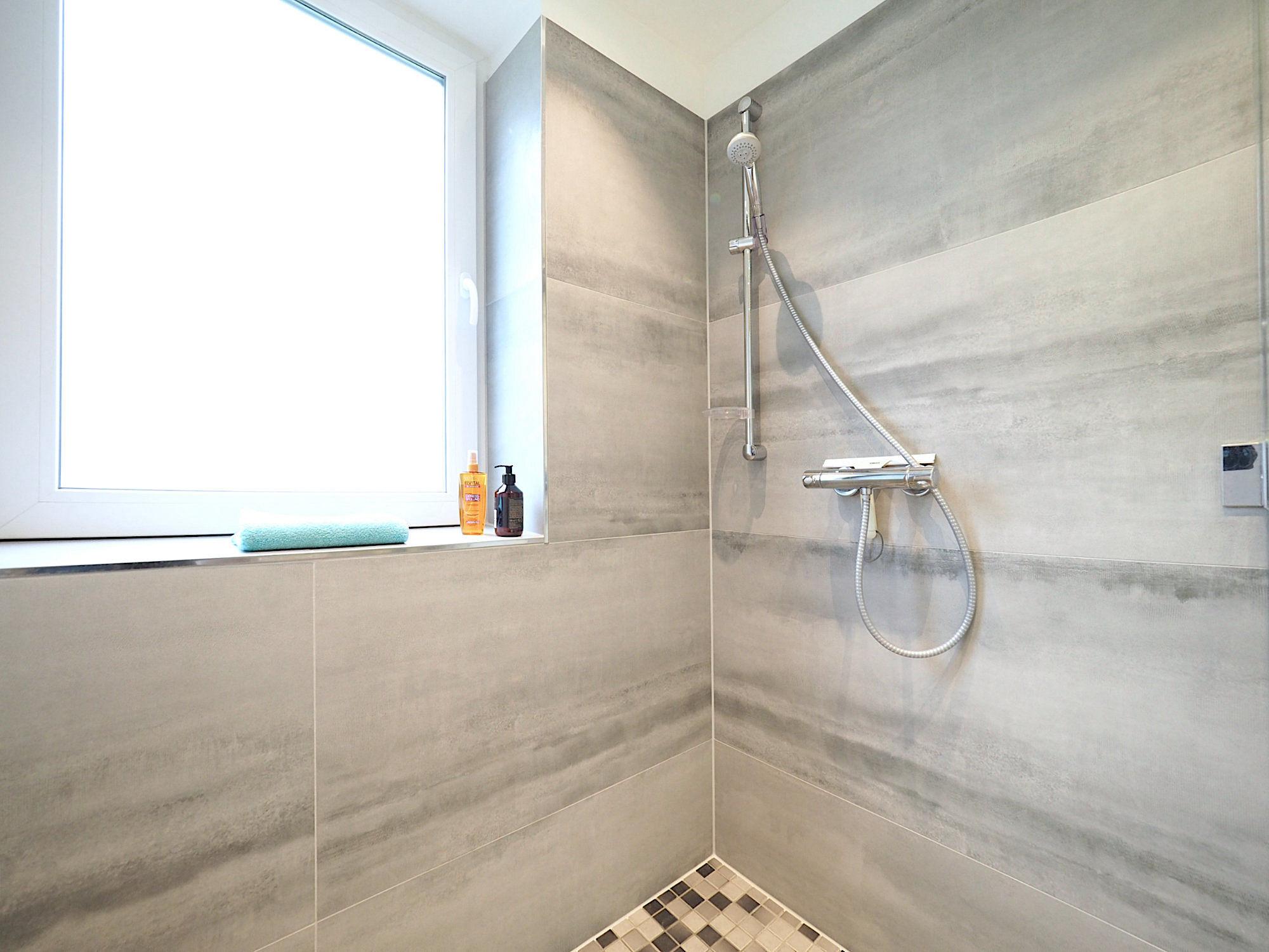 Blick in die geflieste Dusche, im Hintergrund ist ein Fenster