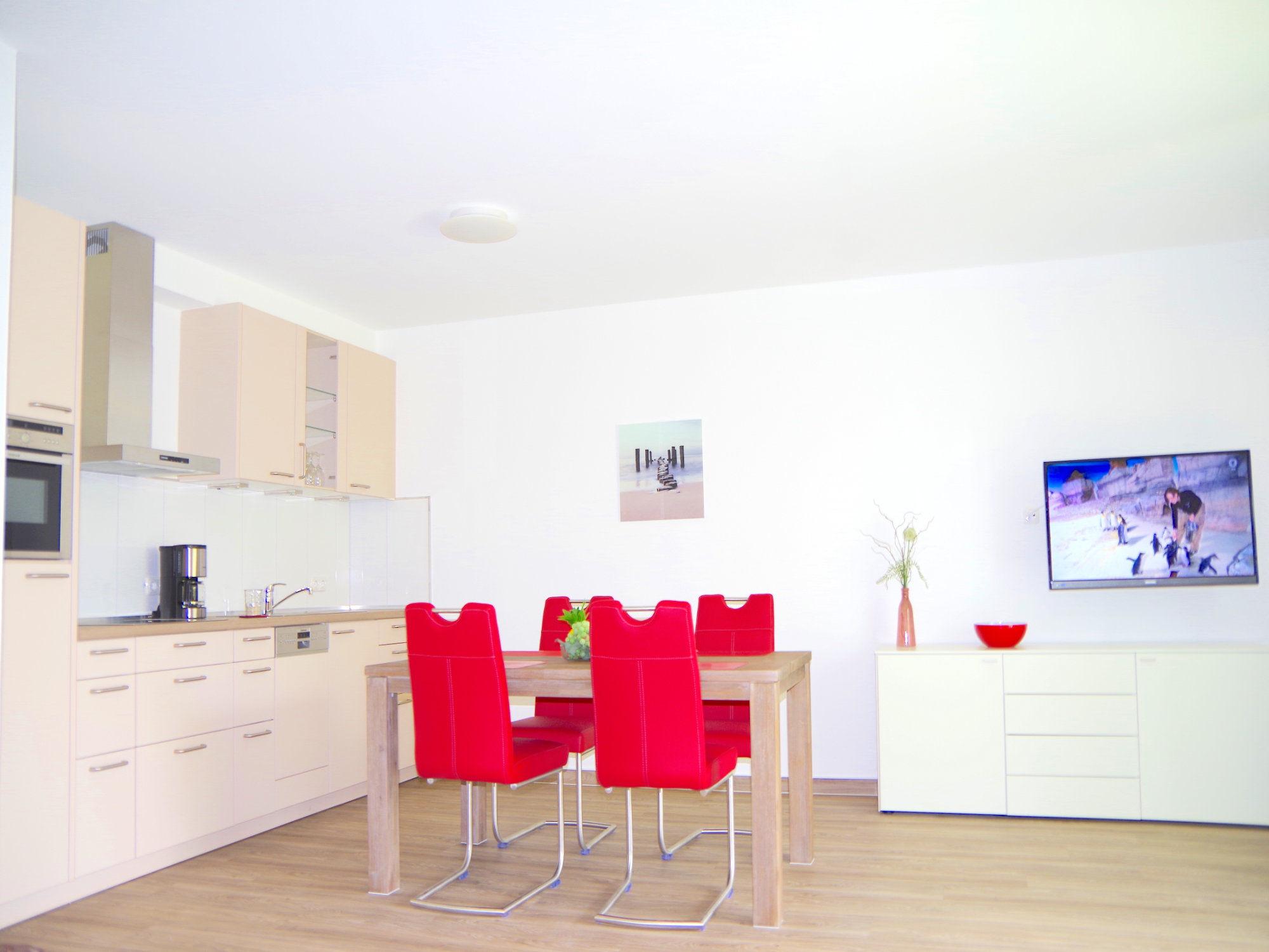 Esstisch mit Stühlen, links dahinter eine moderne Küchenzeile, rechts von dem Esstisch ein Sideboard