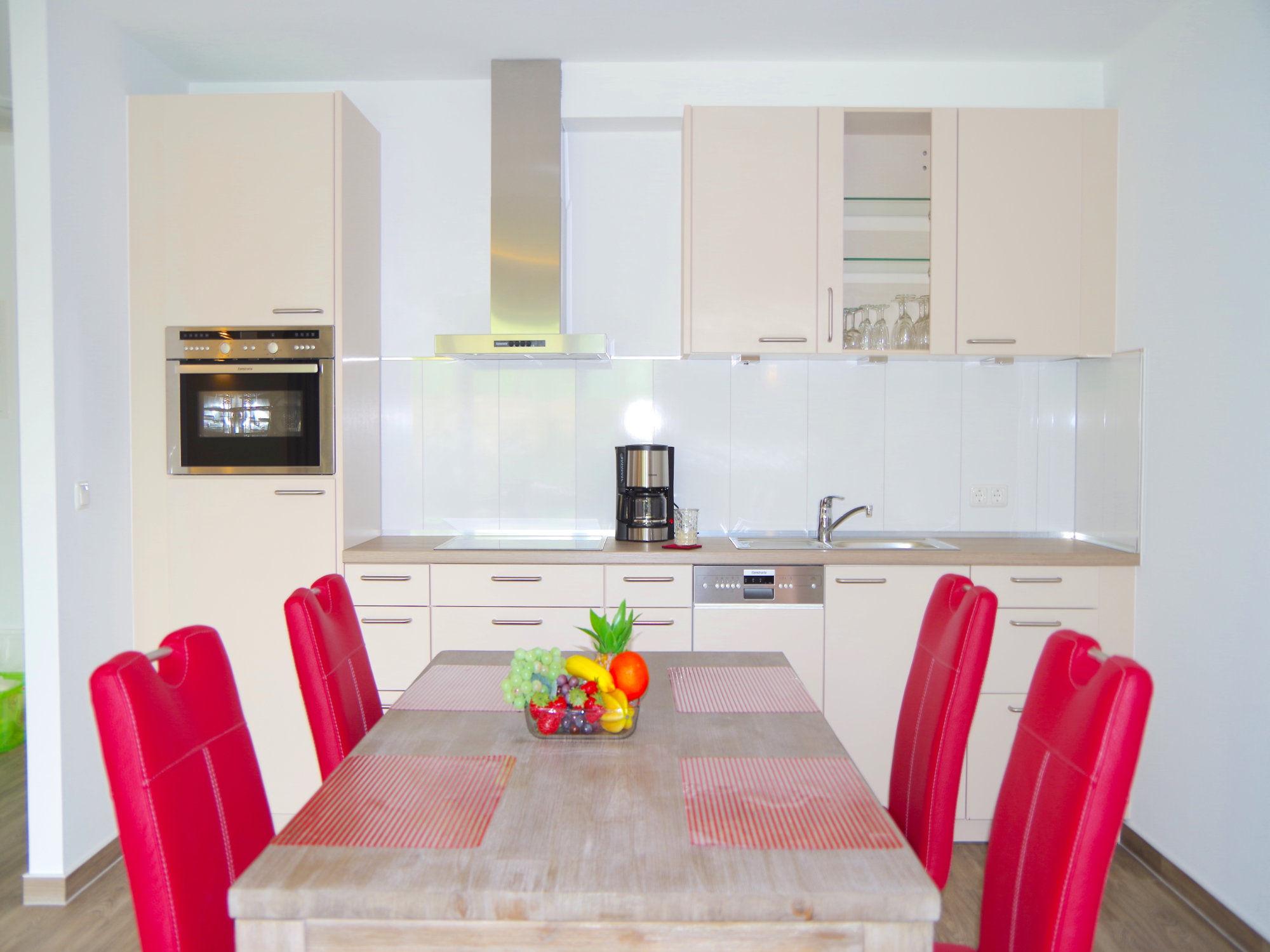 Esstisch mit vier Stühlen, dahinter eine moderne Küchenzeile mit elektrischen Geräten