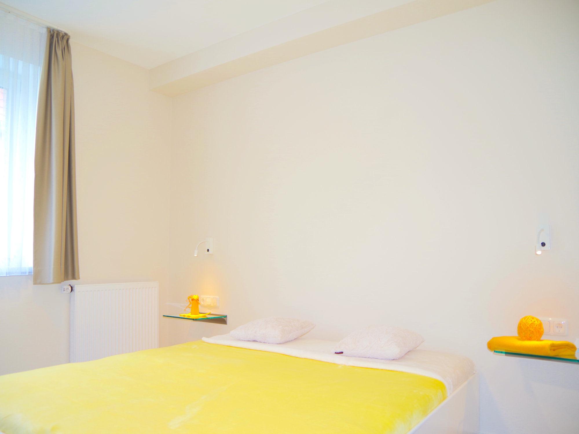 Schlafzimmer  mit Doppelbett und Glaskonsolen neben dem Bett, auf der linken Seite ein Fenster