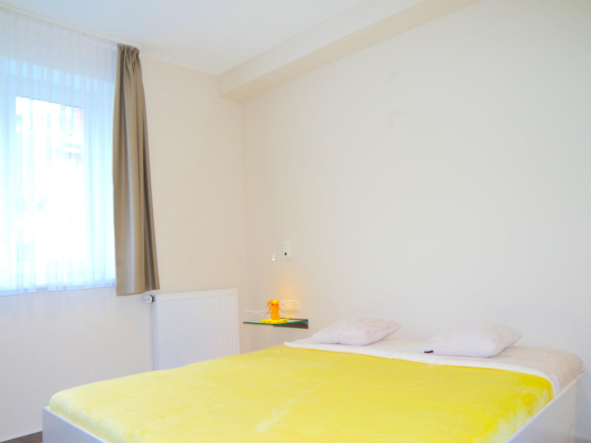 Schlafzimmer  mit Doppelbett und großem Fenster auf der linken Seite