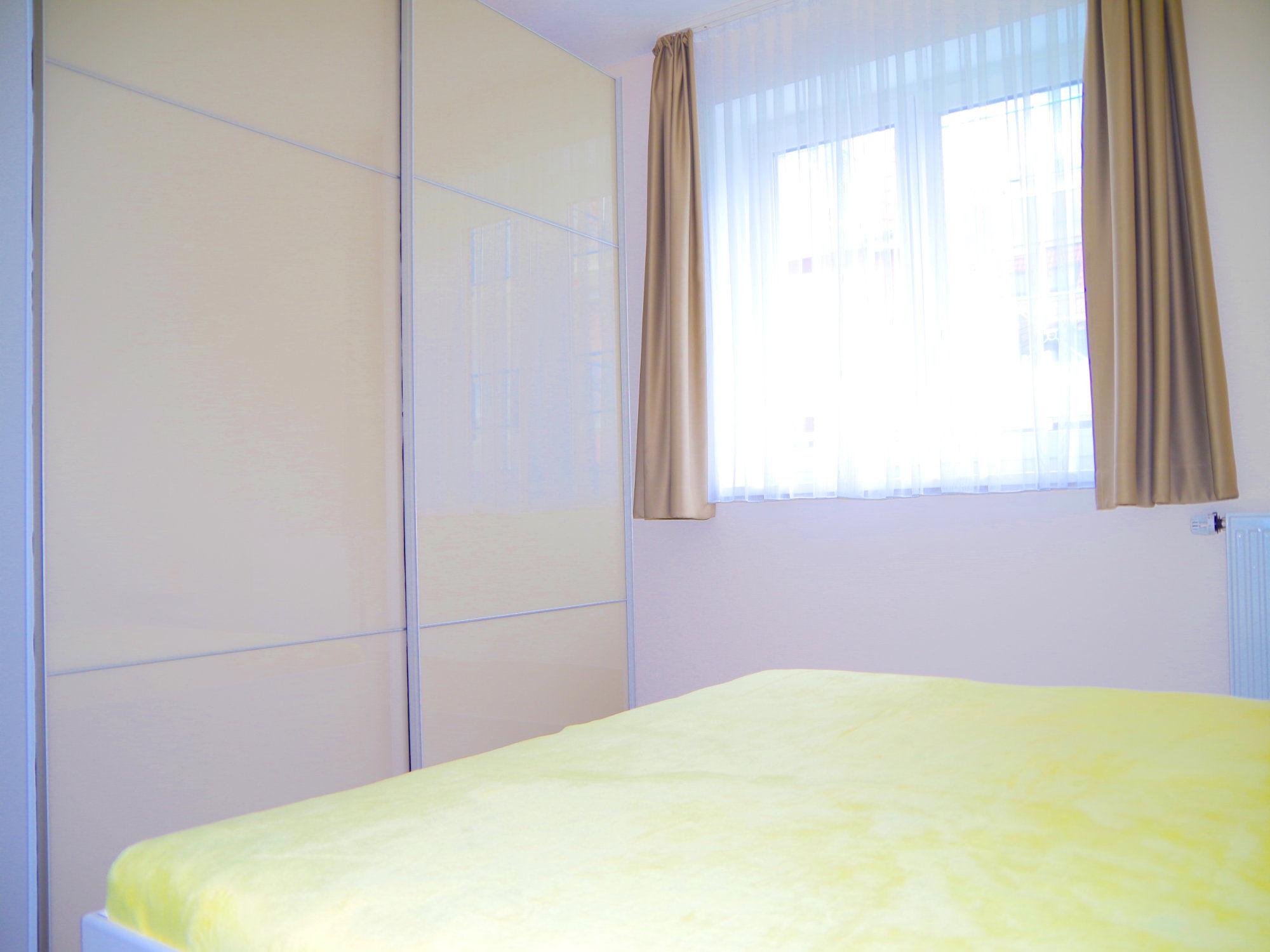 Schlafzimmer  mit Doppelbett, links davon ein großer Kleiderschrank mit Schiebetüren, im Hintergrund ein großes Fenster