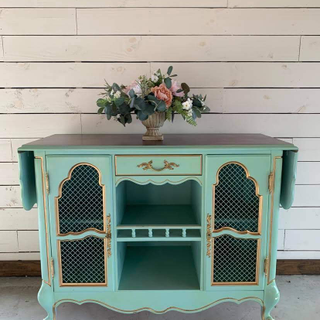 teal table with gold accents and hardware. with wheels