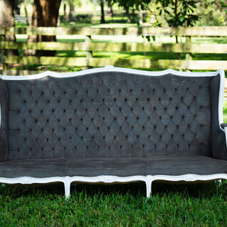 Grey tuffed vintage loveseat with high back and white trim