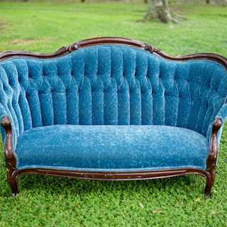Blue tuffed velvet love seat with brown wood trim and legs