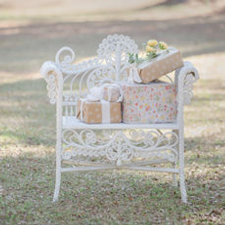 white wicker chair with wrapped presents outside