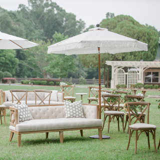 white fringe umbrella set up for an outside ceremony with sofas for social distancing