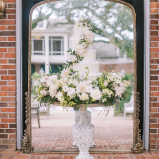 French pedestal table with wedding cake in front of large Primrose mirror.  Photo by Jenna Lindsey.