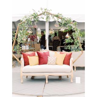 Linen settee in front of heptagon wooden arbor
