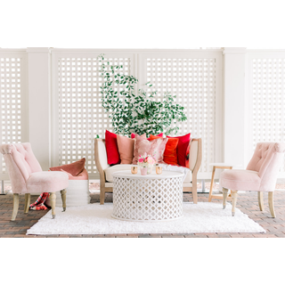 Linen sofa, two pink chairs, white coffee table with red and pink pillows