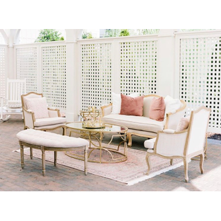 Linen loveseat, two linen chairs, linen bench, gold coffee and side tables with pink pillows and rug